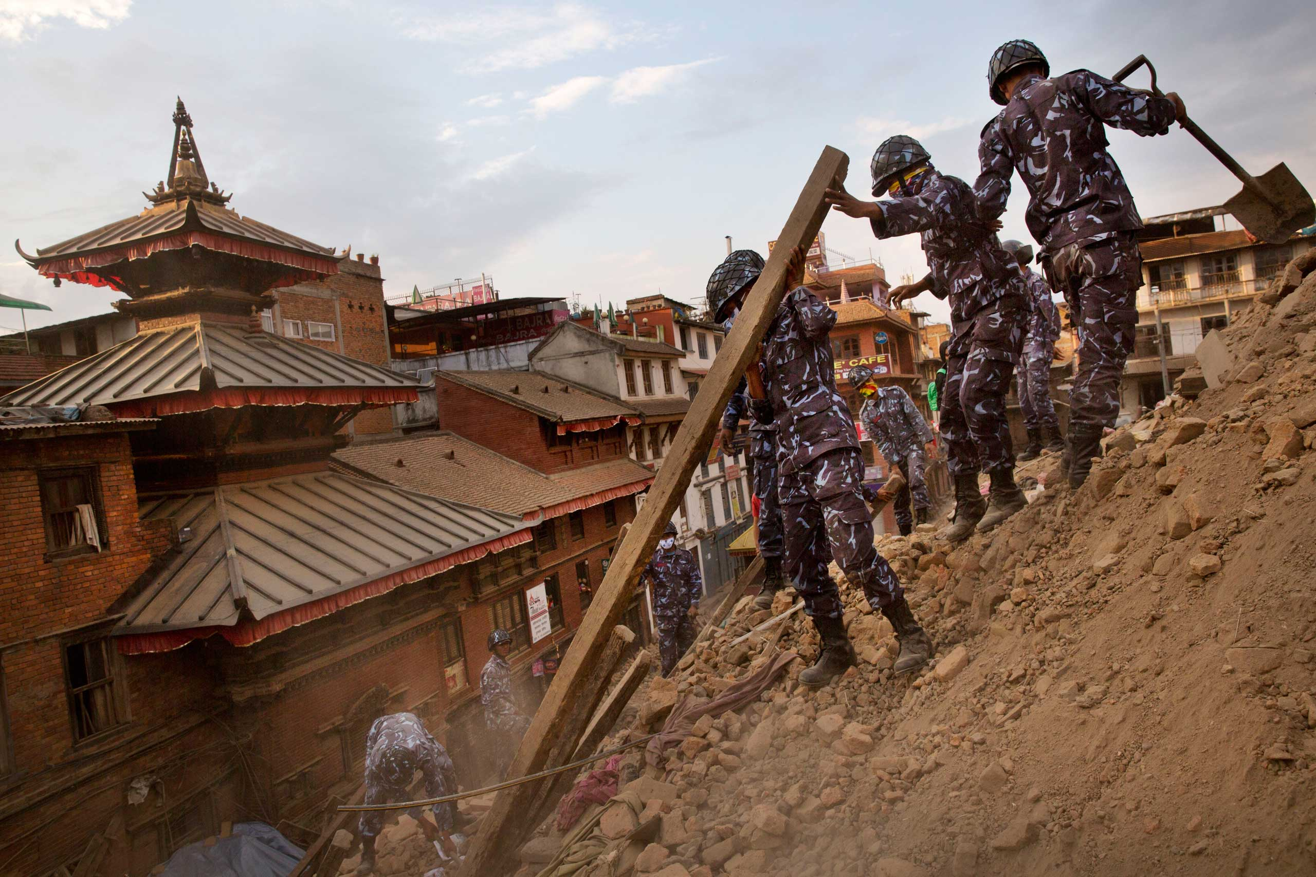 Nepalese policemen clear the debris at Basantapur Durbar Square, damaged in Saturday's earthquake, in Kathmandu on April 26, 2015.