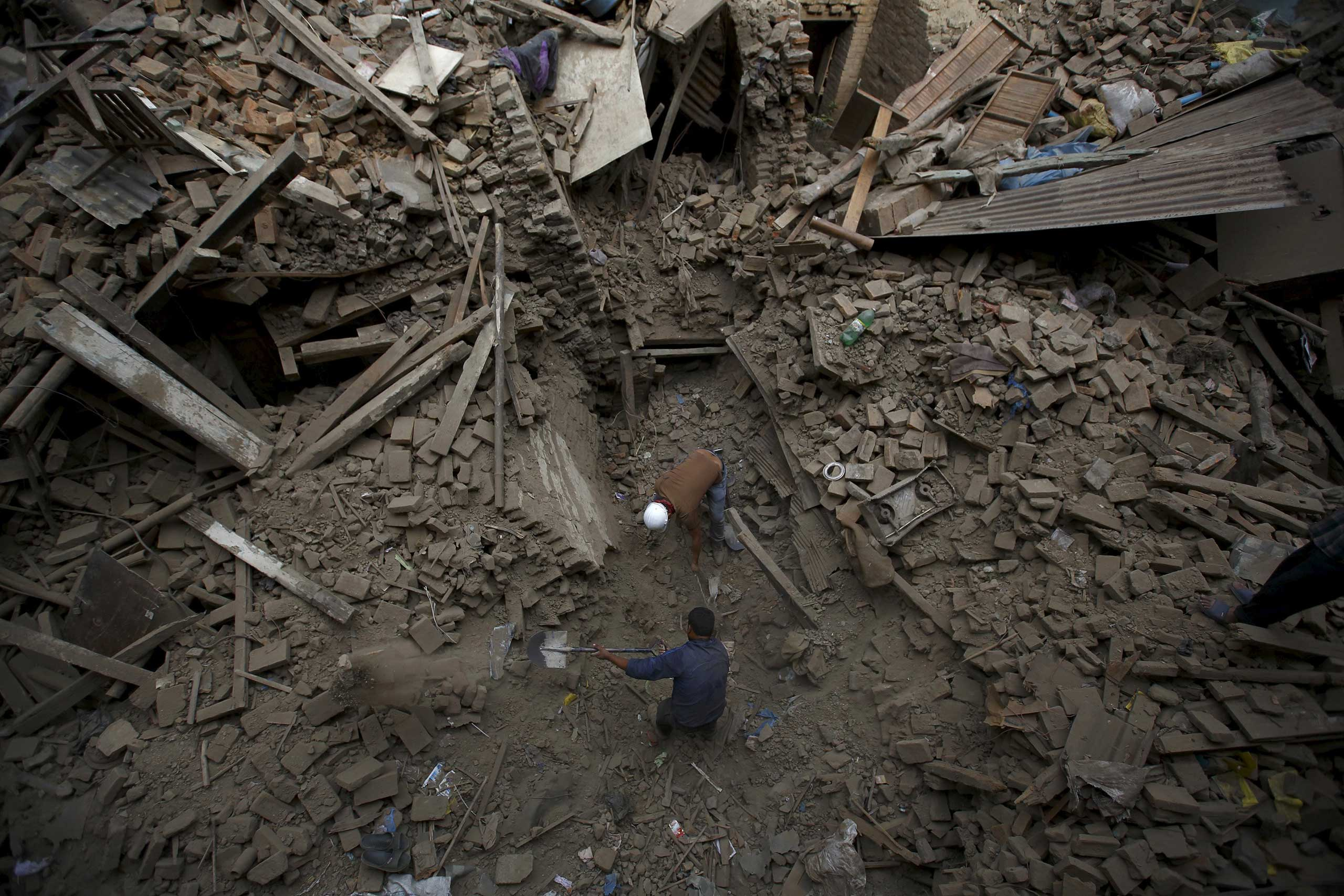 People search for family members trapped inside collapsed houses a day after an earthquake in Bhaktapur, Nepal on April 26, 2015.