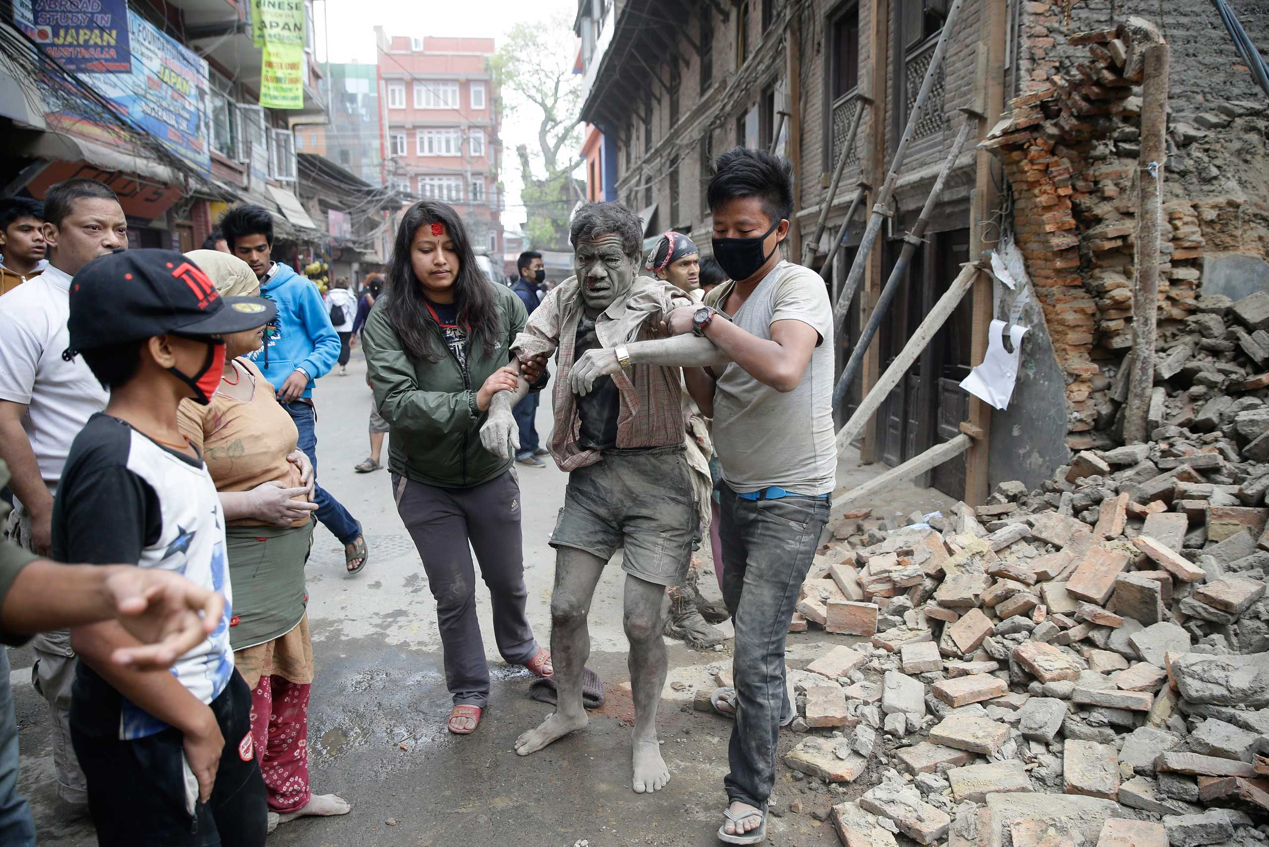 People free a man from the rubble of a destroyed building after an earthquake in Kathmandu, Nepal on April 25, 2015.