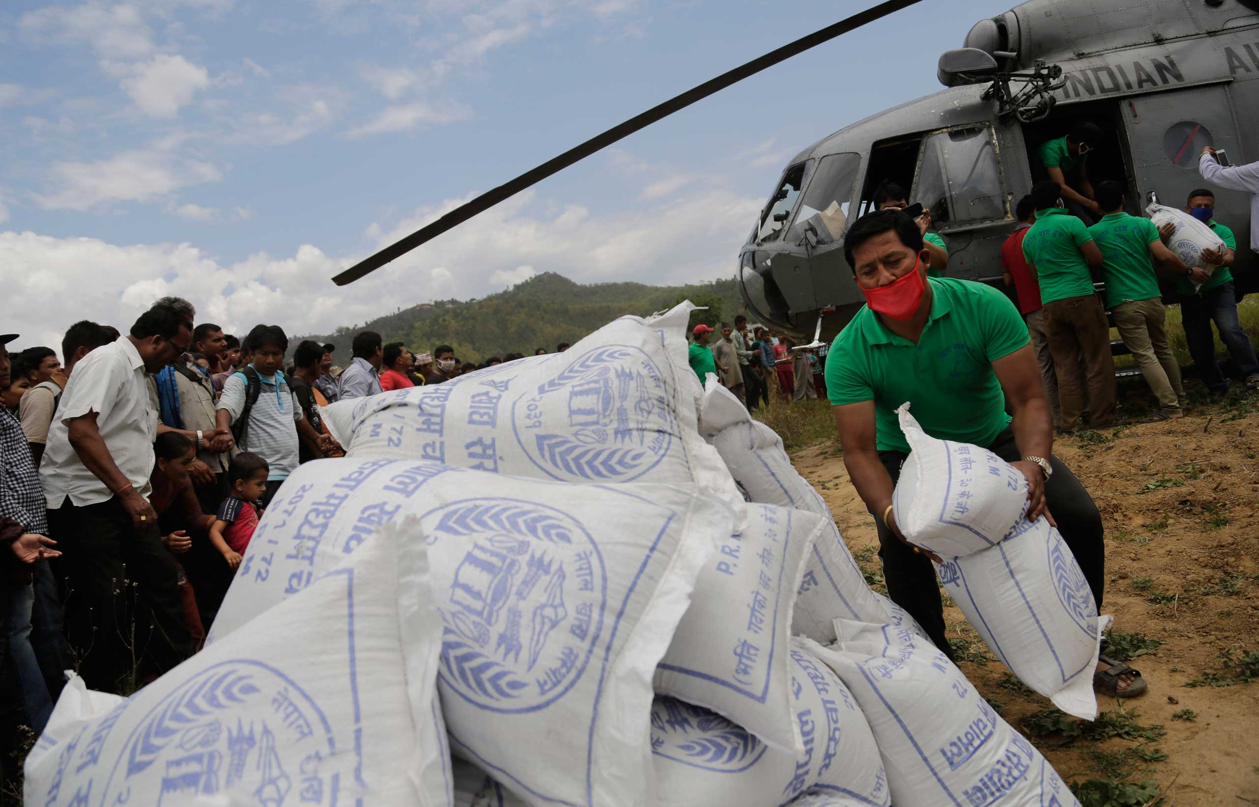 Nepalese volunteers unload relief material, brought by an Indian Air Force helicopter for victims of Saturday's earthquake at Trishuli Bazar in Nepal on April 27, 2015.