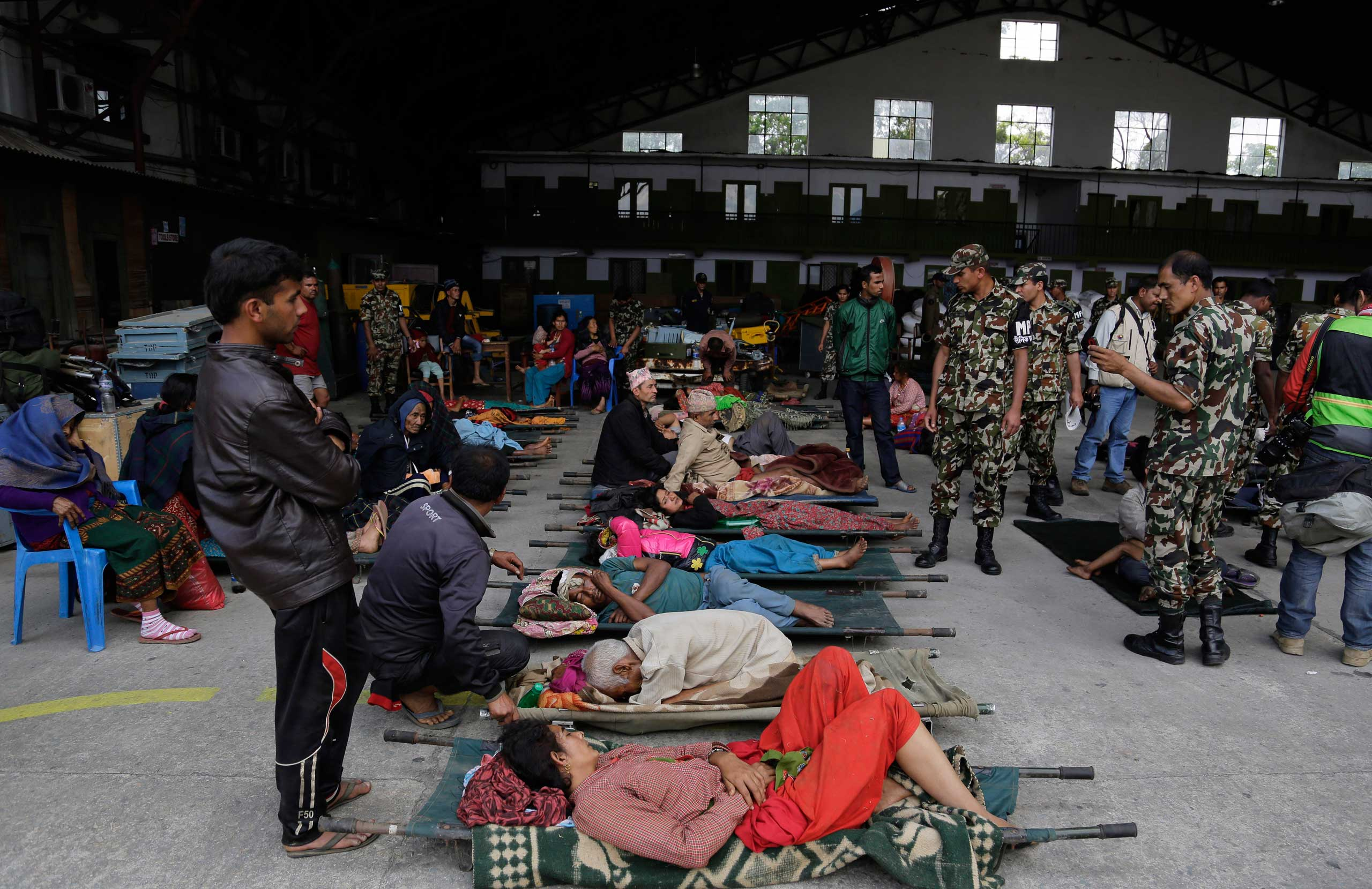 Victims of Saturday's earthquake wait for ambulances to take them to hospitals after being evacuated at the airport in Kathmandu, Nepal, on April 27, 2015.