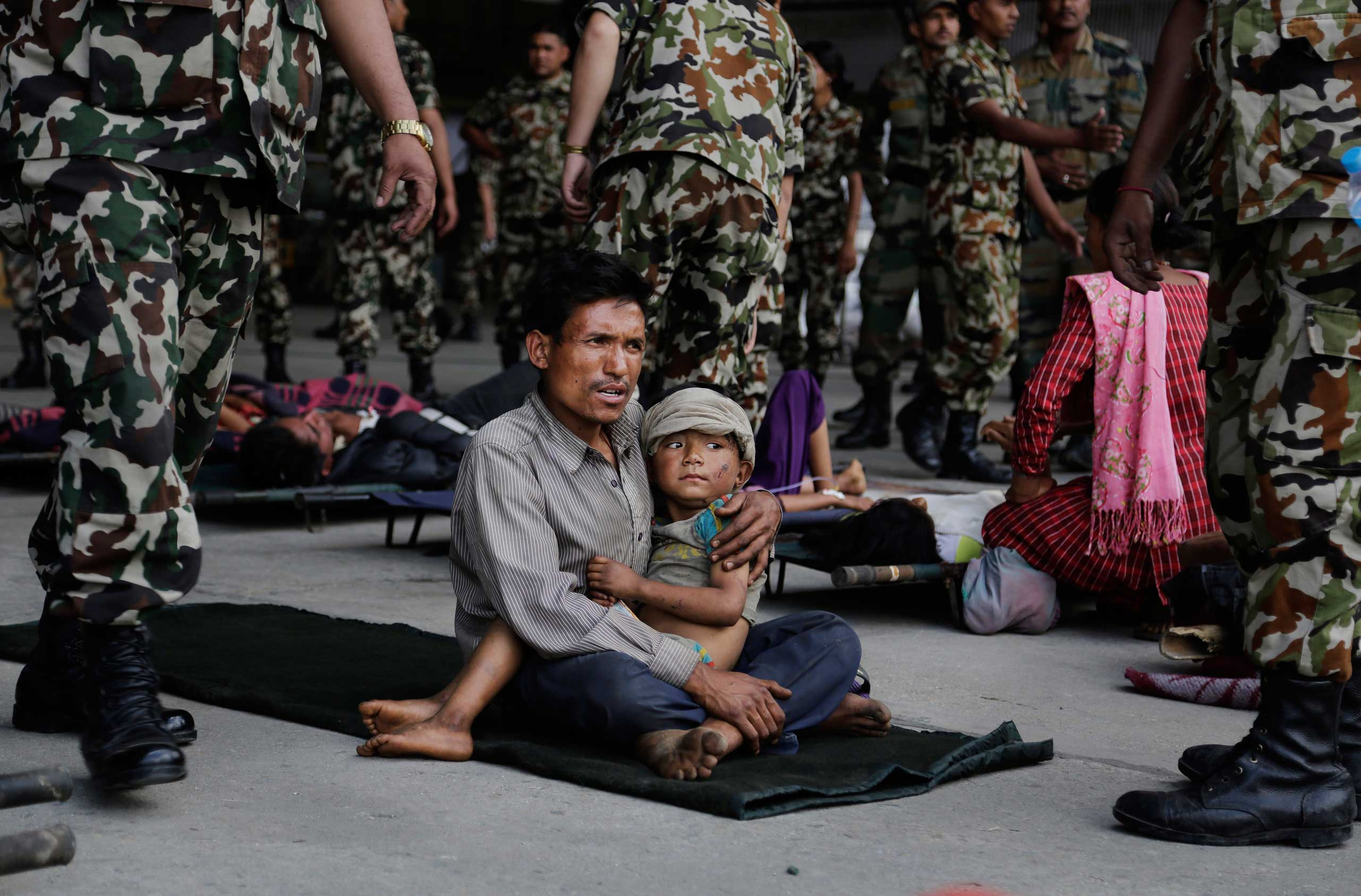 A man sits with a child on his lap as victims of Saturday's earthquake wait for ambulances after being evacuated at the airport in Kathmandu, Nepal, on  April 27, 2015.
