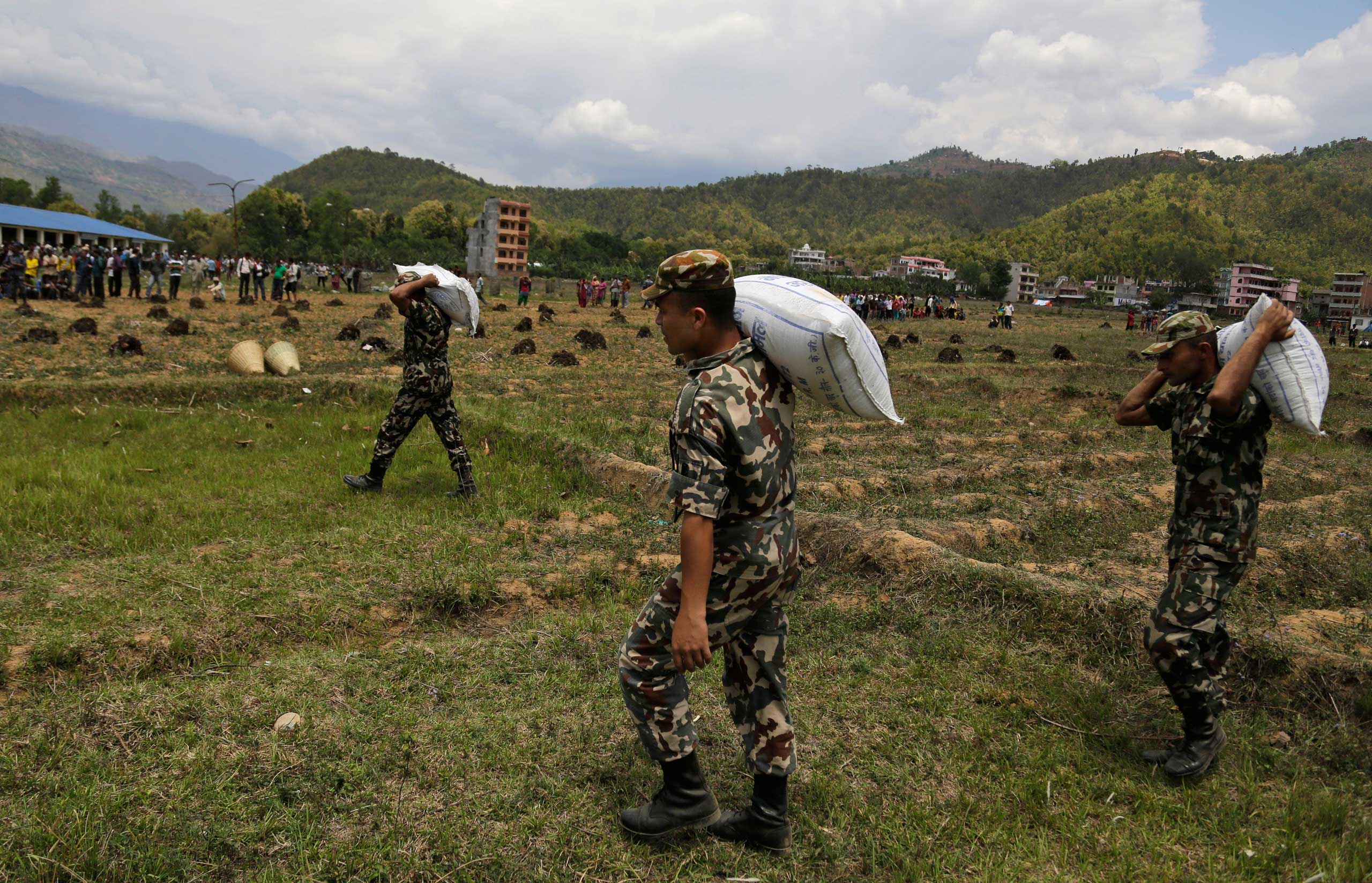 Nepalese soldiers unload relief material brought in by an Indian Air Force helicopter for victims of Saturday's earthquake at Trishuli Bazar in Nepal on April 27, 2015.