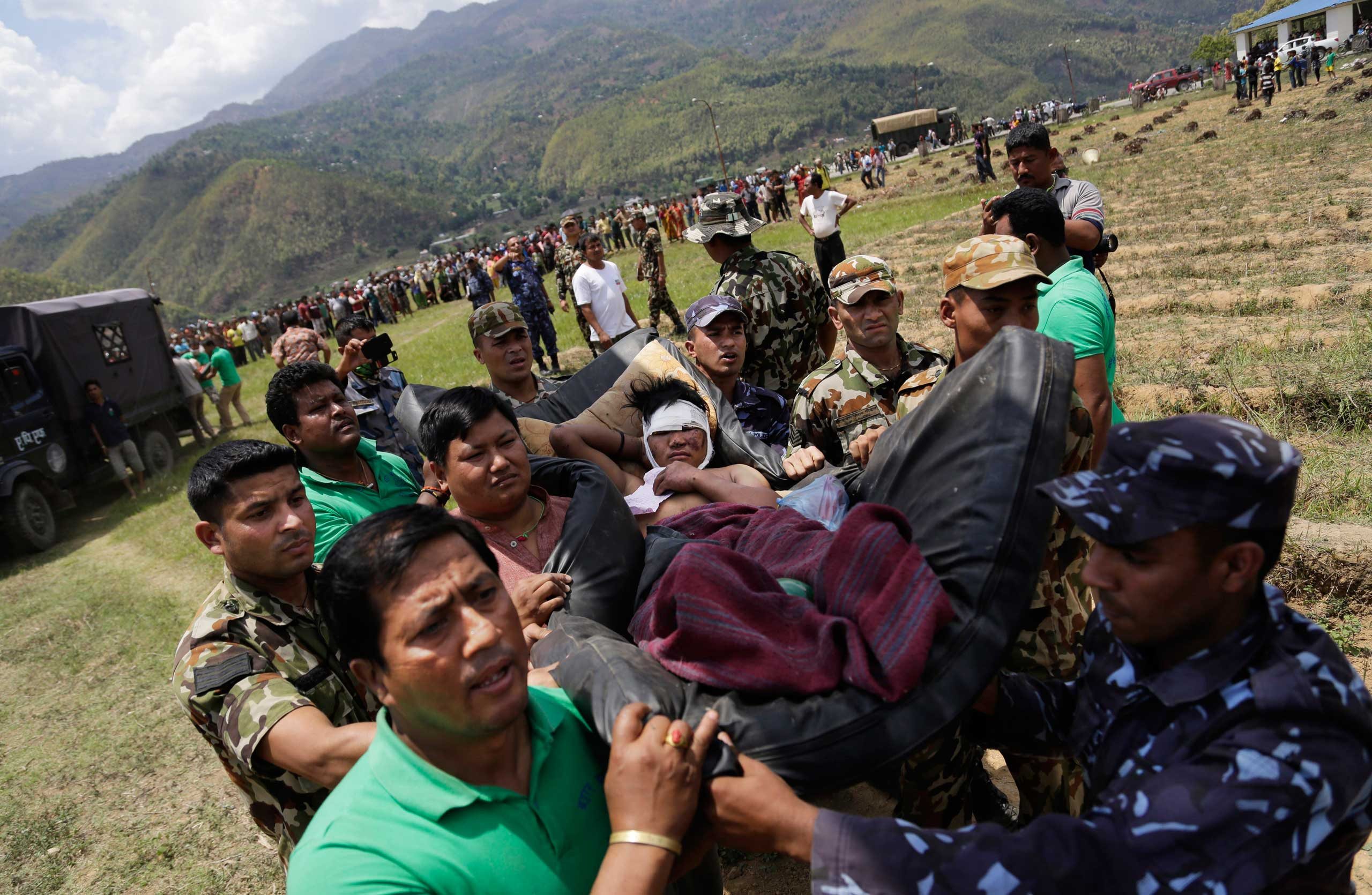 Nepalese soldiers carry a wounded man on a makeshift stretcher to an Indian Air Force helicopter as they evacuate victims of Saturday's earthquake from Trishuli Bazar to Kathmandu airport in Nepal on April 27, 2015.