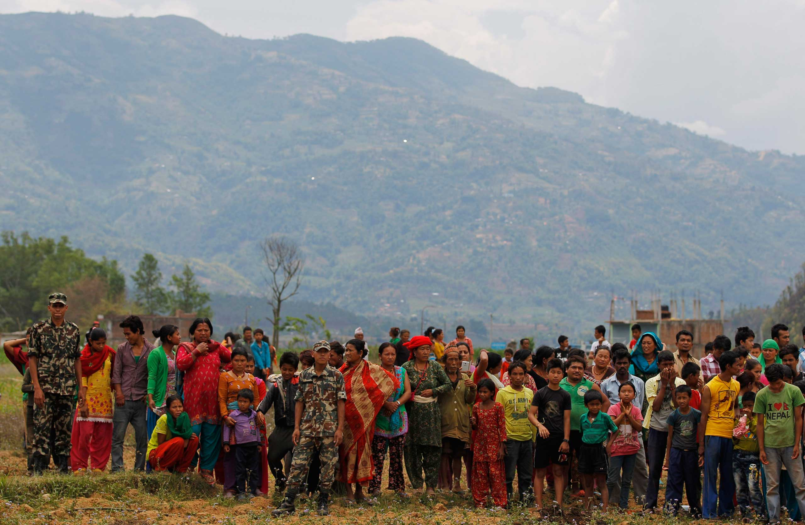 Nepalese villagers watch as relief material is brought in by an Indian Air Force helicopter for victims of Saturday's earthquake at Trishuli Bazar in Nepal on April 27, 2015.