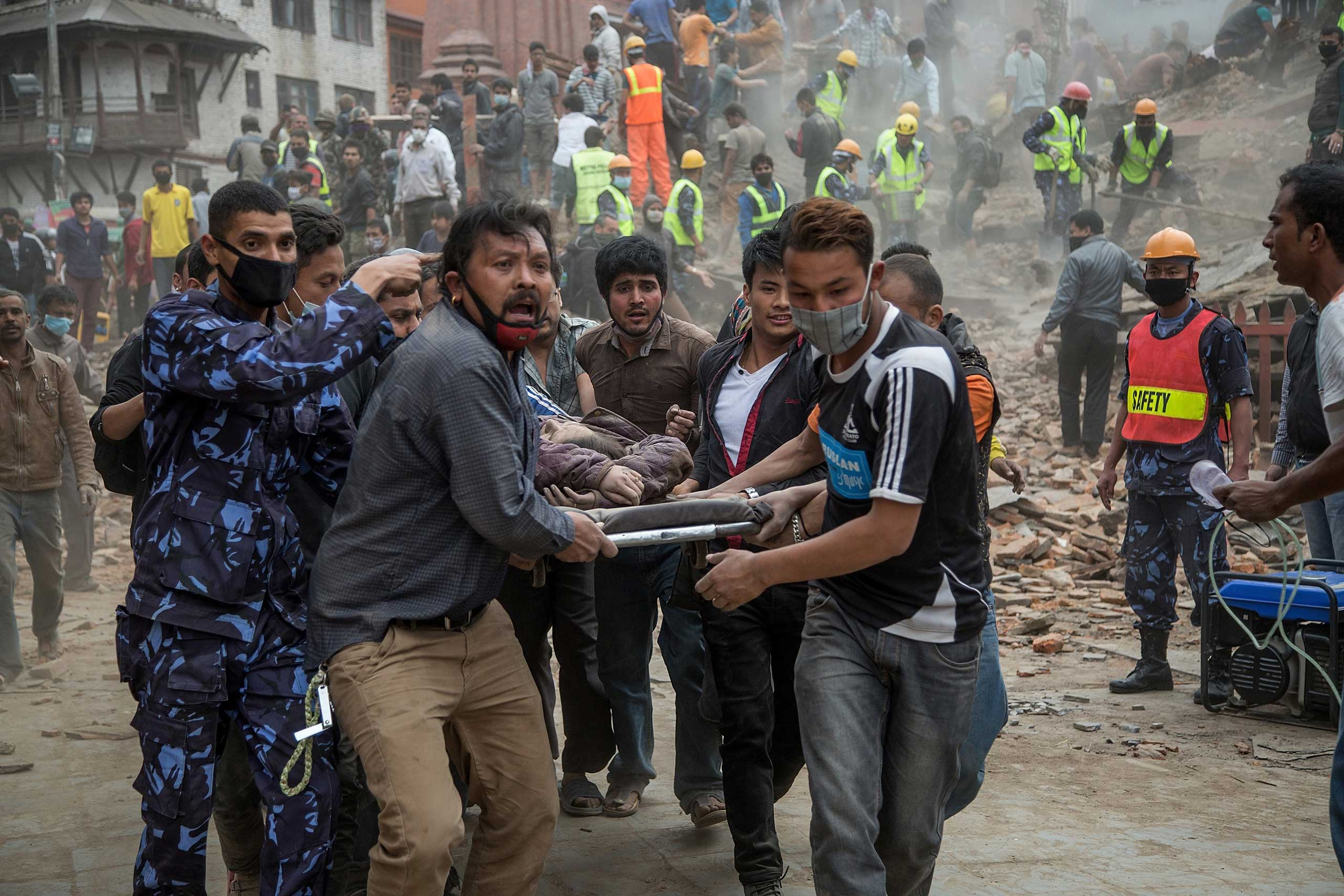 People carry a victim who was removed from the collapsed Dharara tower  following the earthquake in Kathmandu.