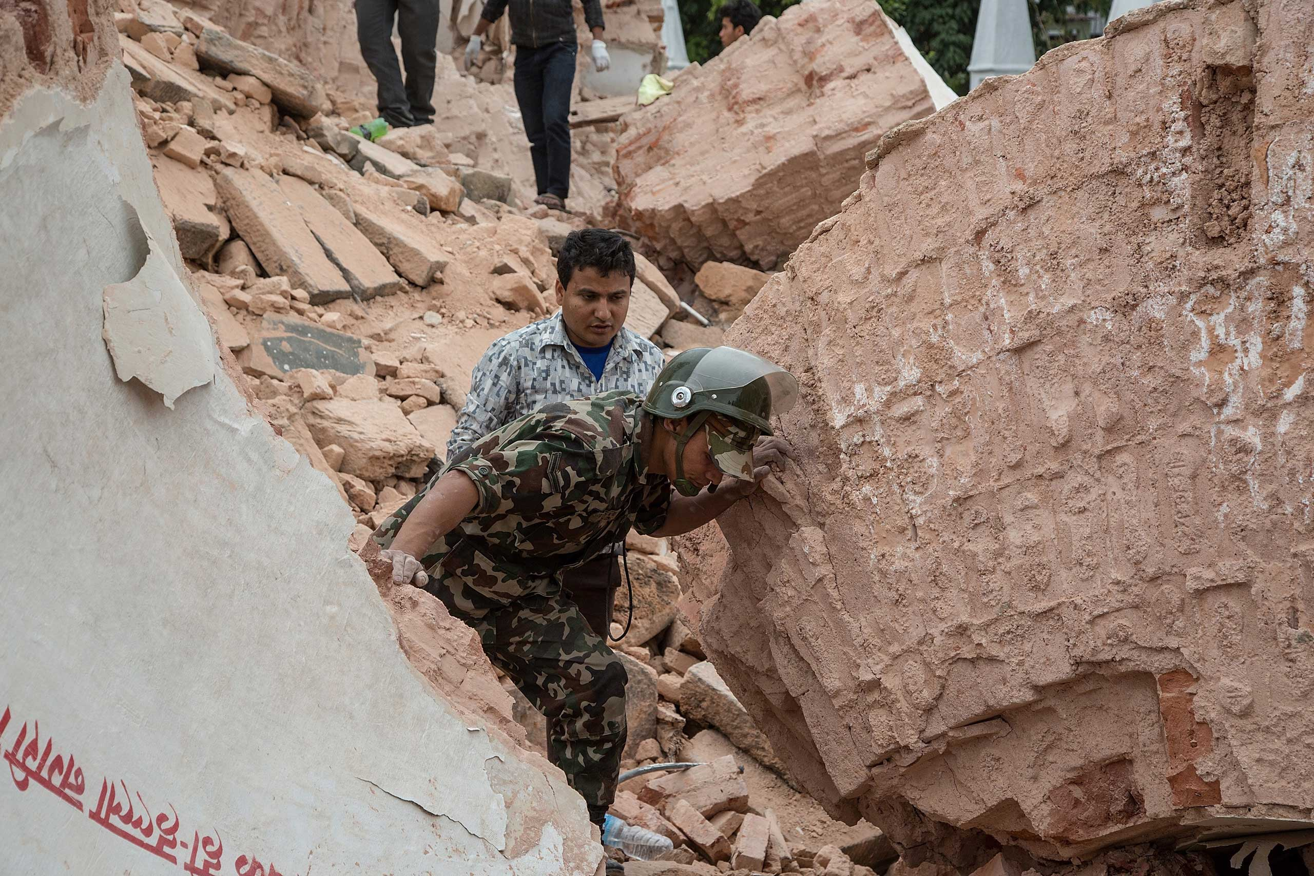Emergency rescue workers search for survivors in the debris of Dharara tower in Kathmandu after it collapsed.
