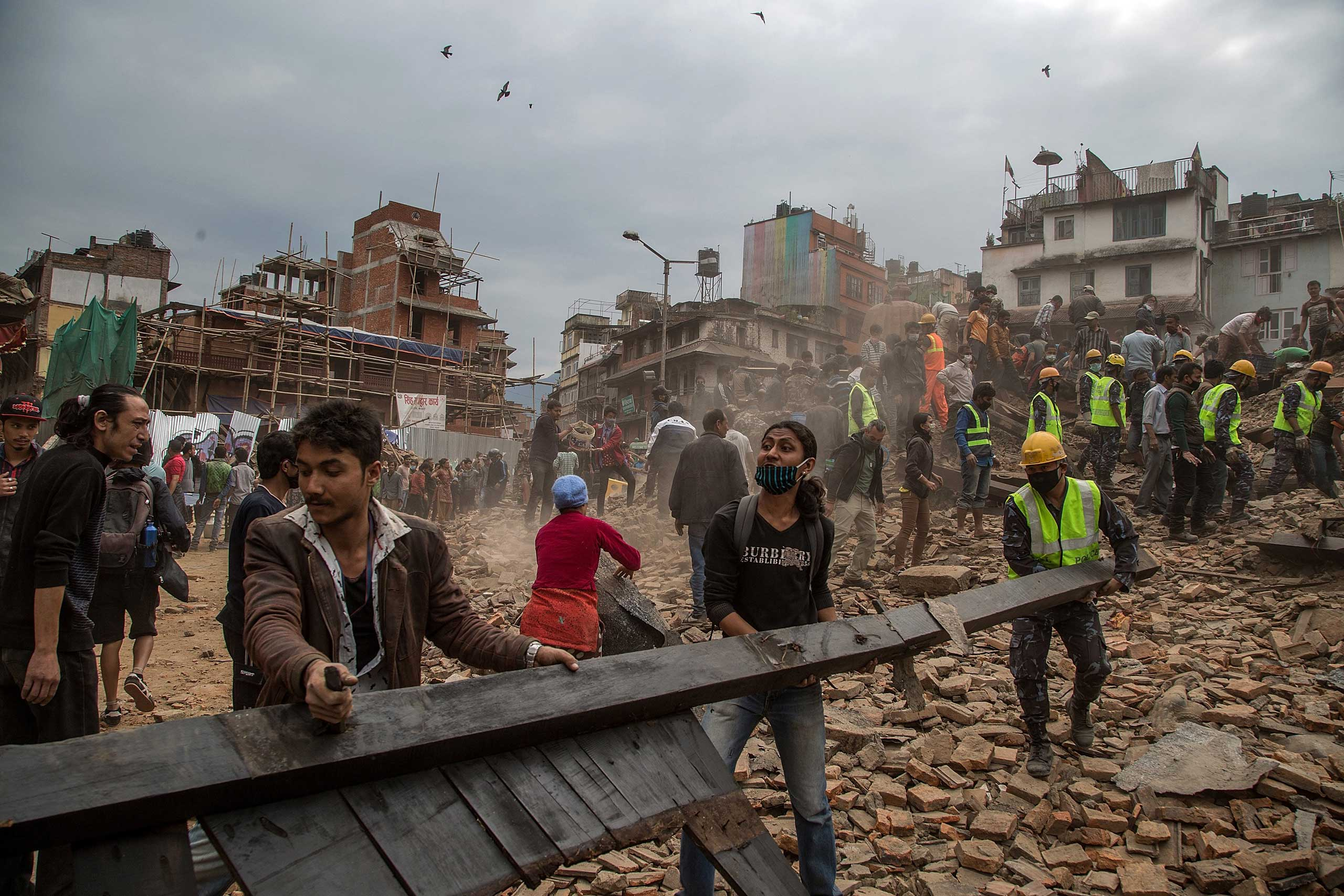 People clear debris in Basantapur Durbar Square while searching for survivors in Kathmandu.