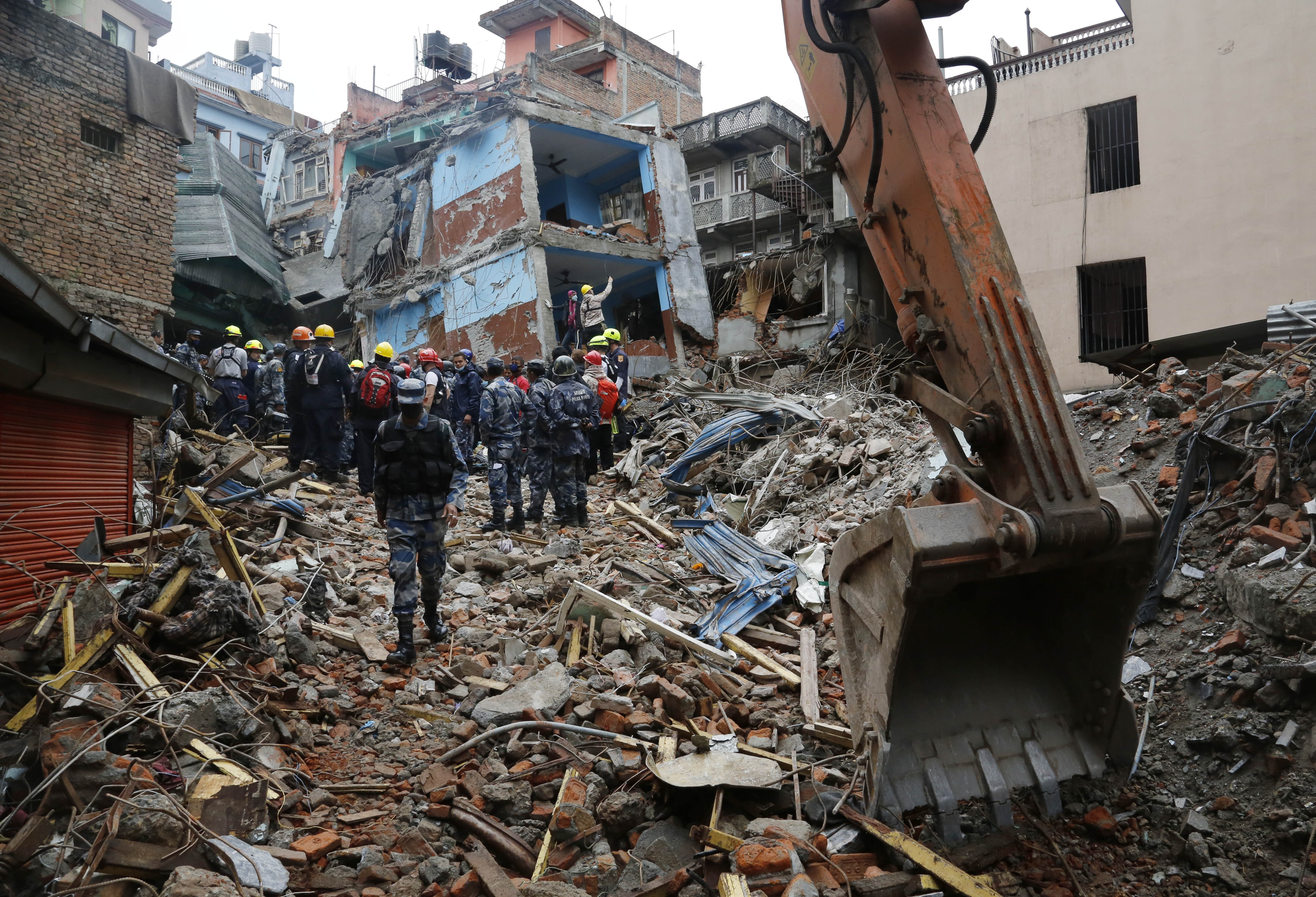 Nepal policemen cordon off the area as they and US rescue workers prepare to  pull out Pemba Tamang, a teenage boy from the rubble of a building five days after the earthquake in Kathmandu, Nepal, Thursday, April 30, 2015. Crowds cheered Thursday as Tamang was pulled, dazed and dusty, from the wreckage of a seven-story Kathmandu building that collapsed around him five days ago when an enormous earthquake shook Nepal. (AP Photo / Manish Swarup)