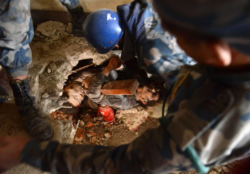 Nepalese rescue personnel help a trapped earthquake survivor, center right, as his friend lies dead next to him in Swyambhu, in Kathmandu on April 26, 2015.