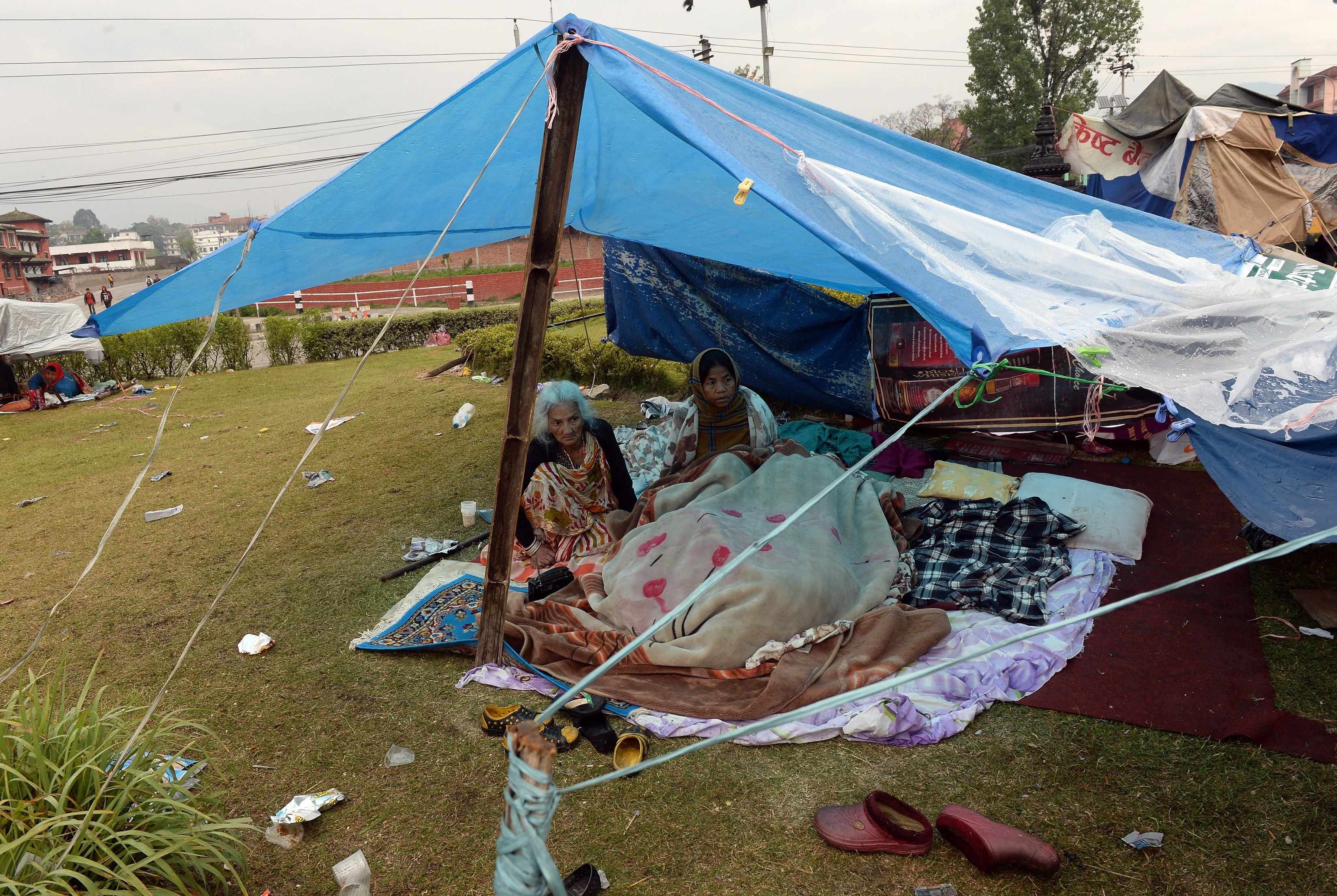 Nepalese people rest in their makeshift shelter next to a road in Kathmandu on April 27, 2015, two days after a 7.8 magnitude earthquake hit Nepal.
