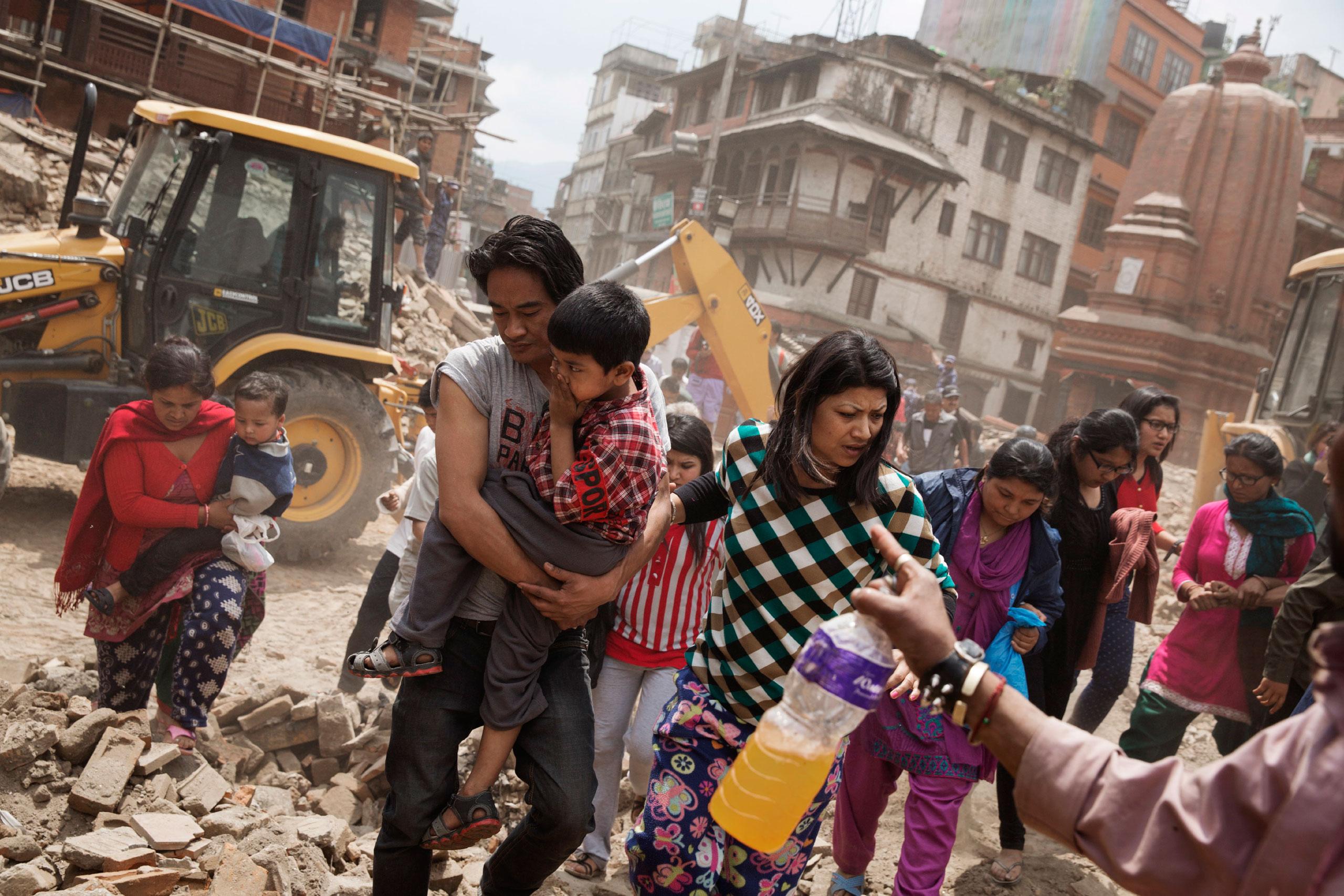 Nepalese people flee buildings during an aftershock in Kathmandu, April 27, 2015.