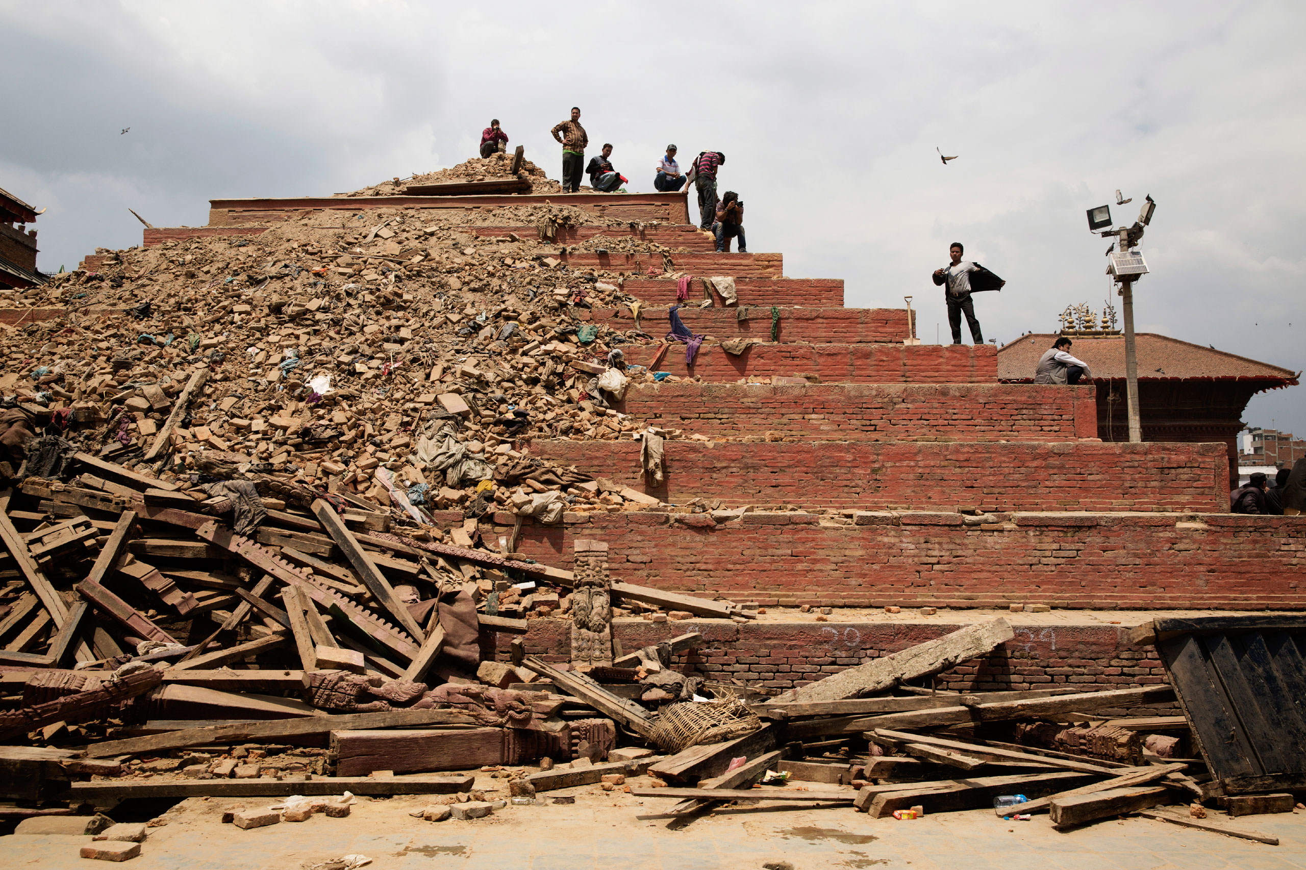 People stand on top of a damaged building in Durbar Square in Kathmandu, April 26, 2015. The historic Durbar Square, a UNESCO world heritage site, was severely damaged in the earthquake.