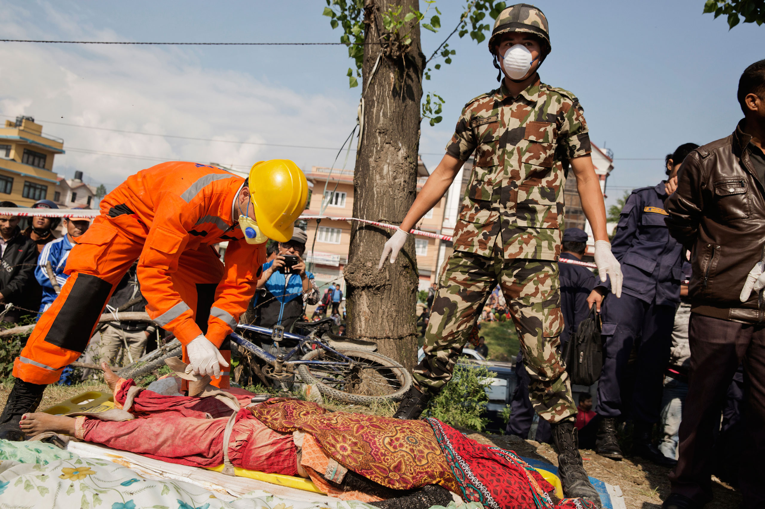 Indian and Nepalese forces attempt to identify a body after it was recovered from a collapsed restaurant in Kathmandu, April 27, 2015.