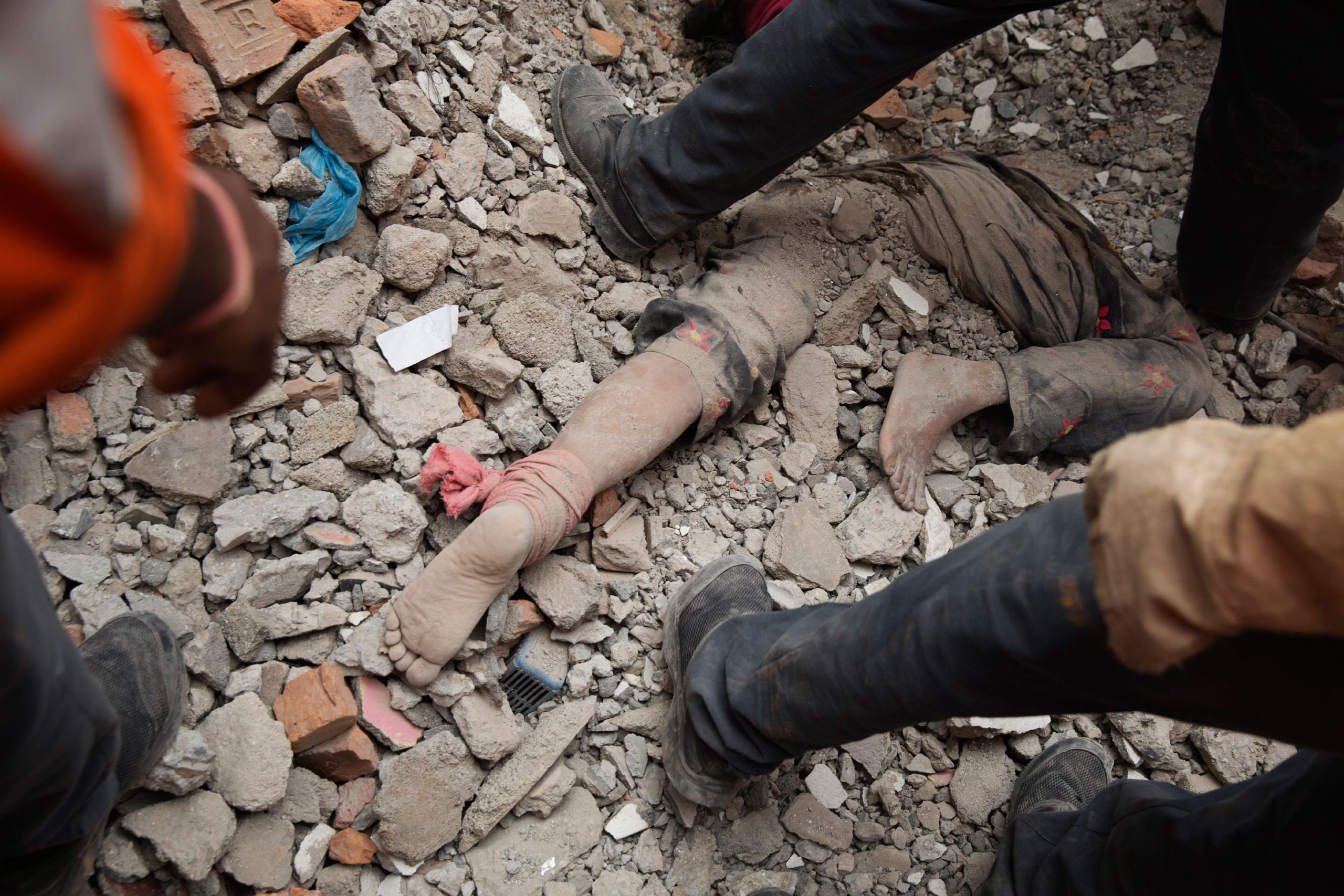 Indian and Nepalese forces excavate a body from collapsed apartments in Kathmandu, April 27, 2015.