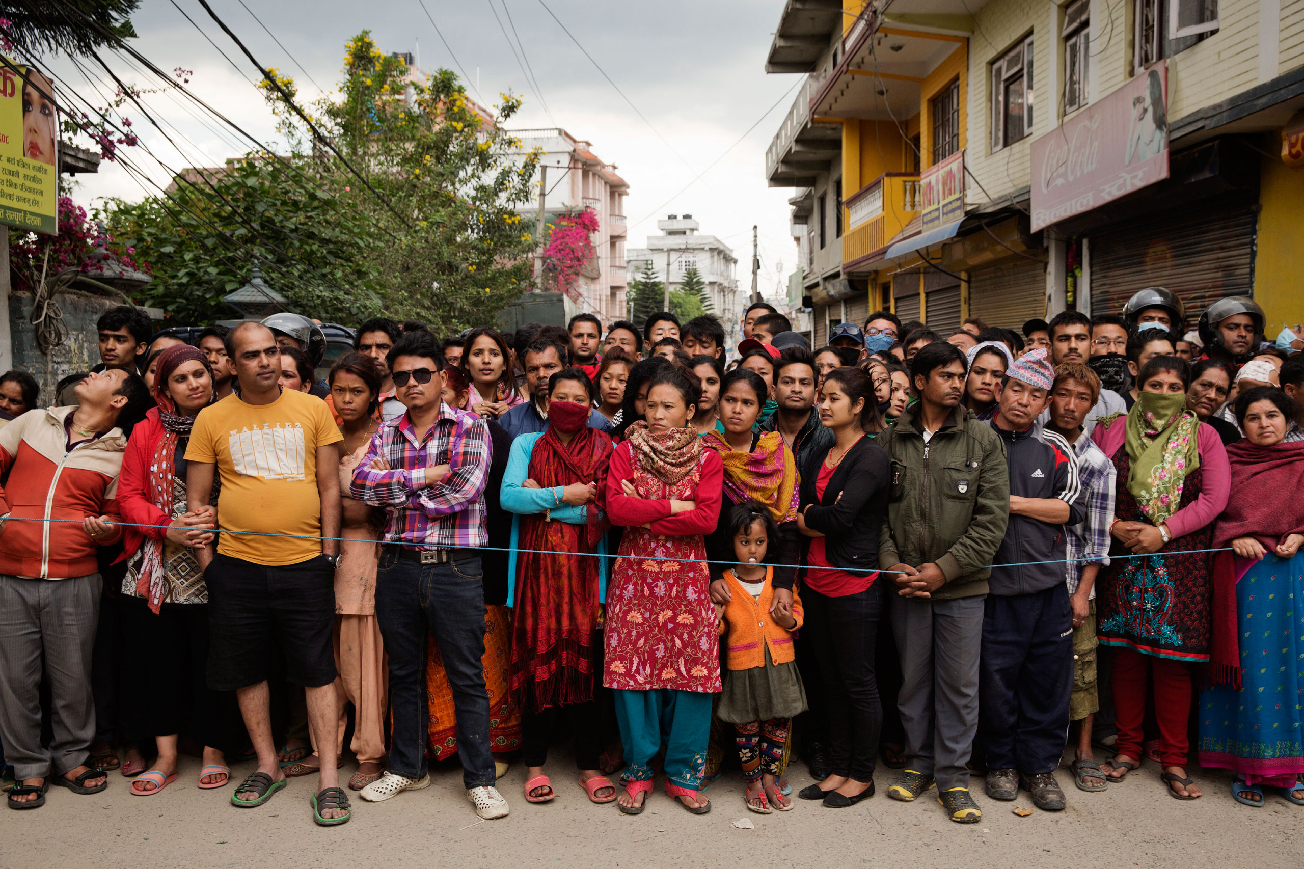 A crowd watches Indian forces excavating collapsed apartments, looking for bodies and survivors in Kathmandu, April 27, 2015.
