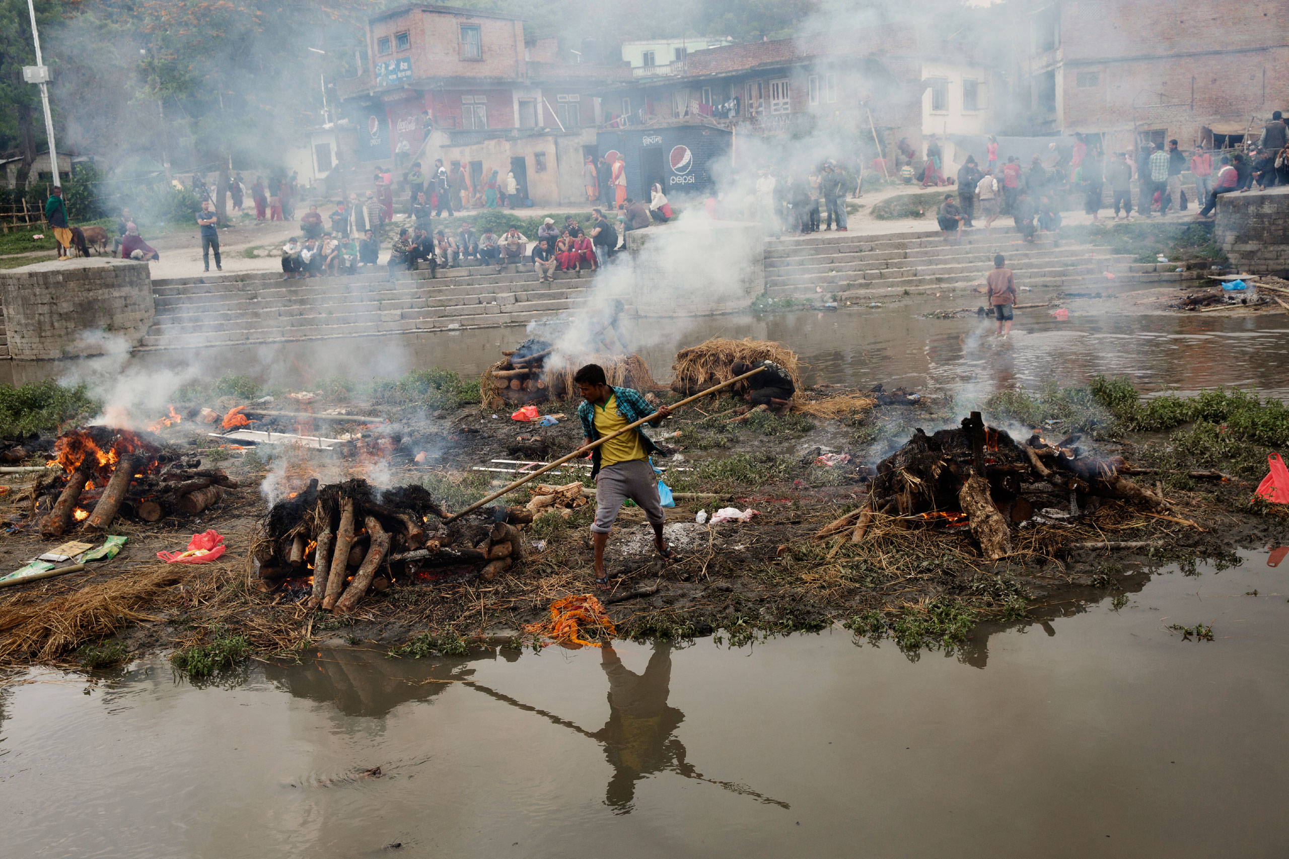 A Hindu Nepalese man tends to a funeral pyre built for a person killed in the earthquake, on the river in Kathmandu, April 27, 2015.