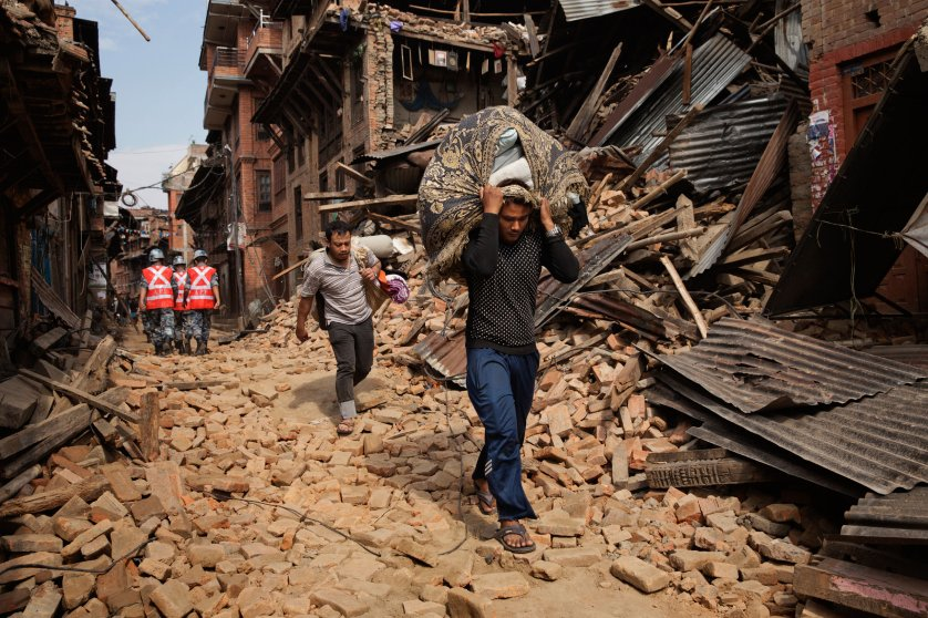 A Nepali man carries recovered belongings through the street in the ancient city of Bhaktapur in the Kathmandu Valley on April. 28, 2015. Nepal had a severe earthquake on April 25th. Photo by Adam Ferguson for Time