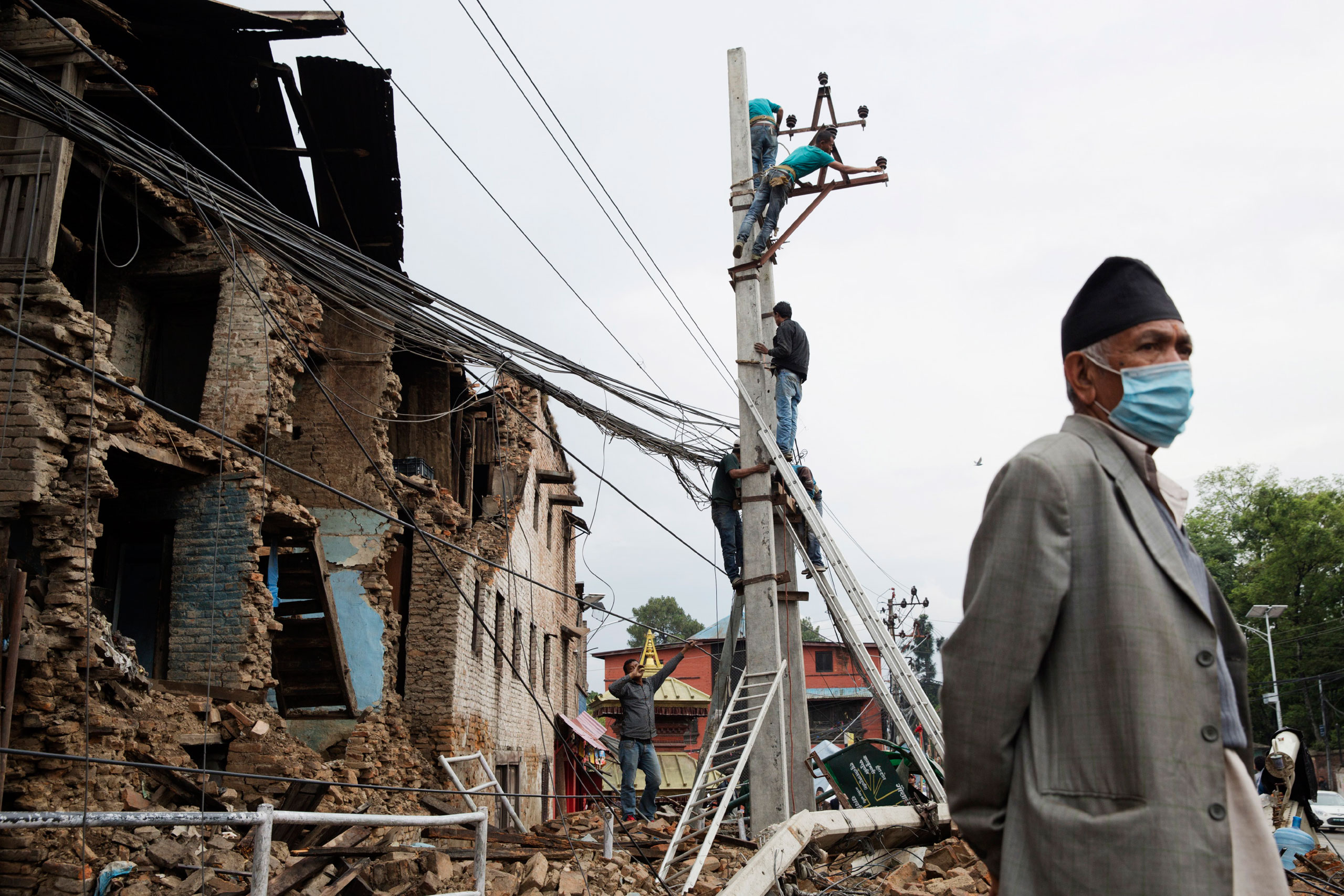 Workers repair power lines in Kathmandu, April 28, 2015.