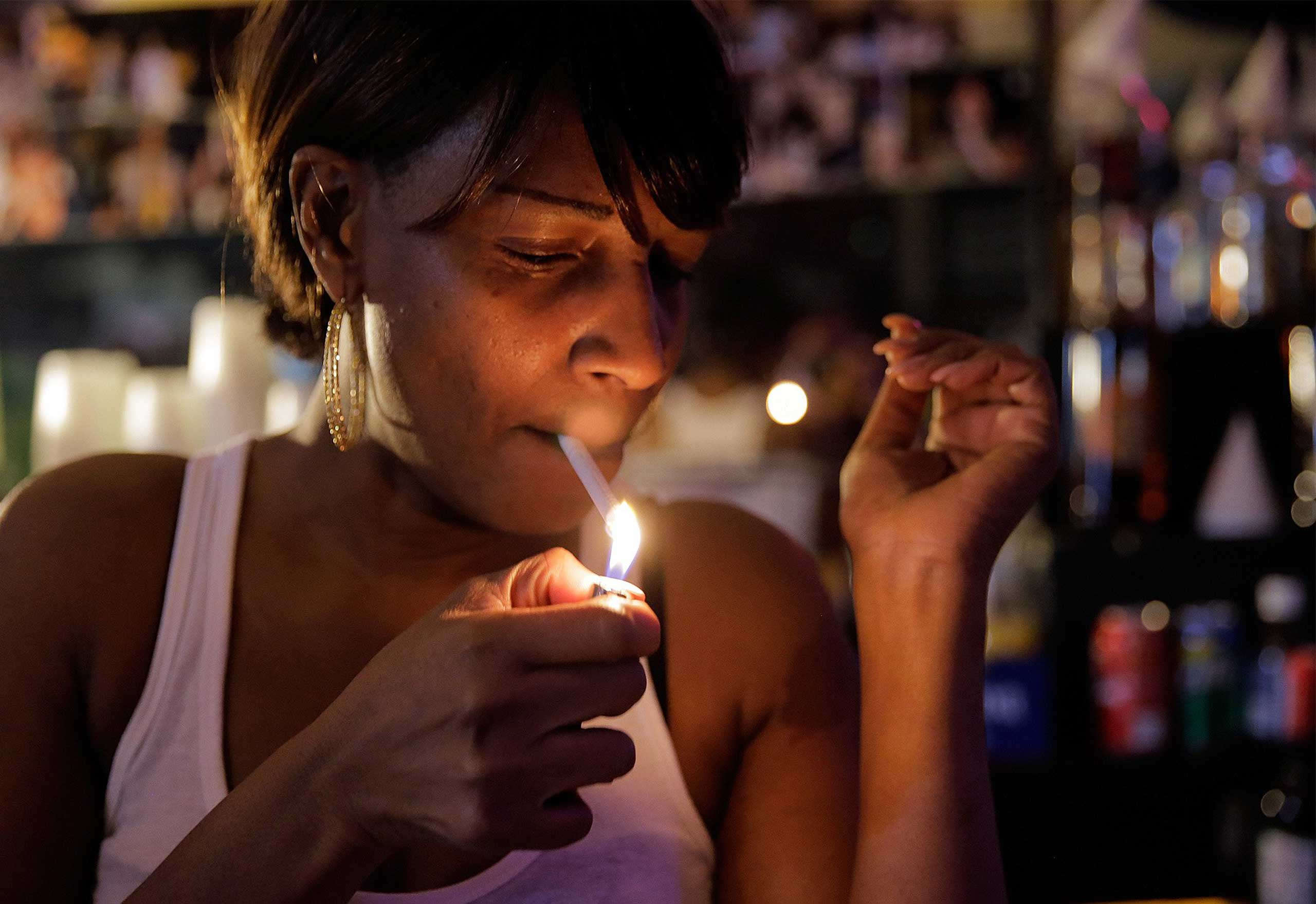 Judy Hill, owner of the Ooh Poo Pah Doo Bar in New Orleans, enjoys a smoke just days before the new city smoking ordinance on April 17, 2015.