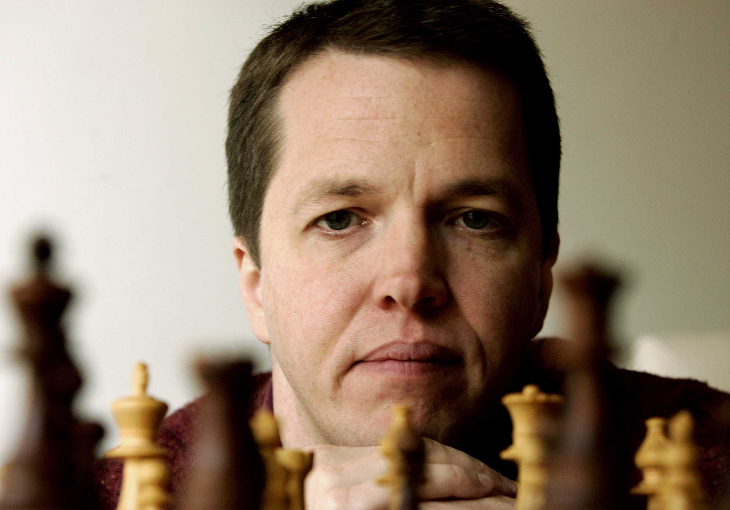 British former World Chess Championhip finalist Nigel Short looks at a chess board in his home in Athens November 4, 2005.