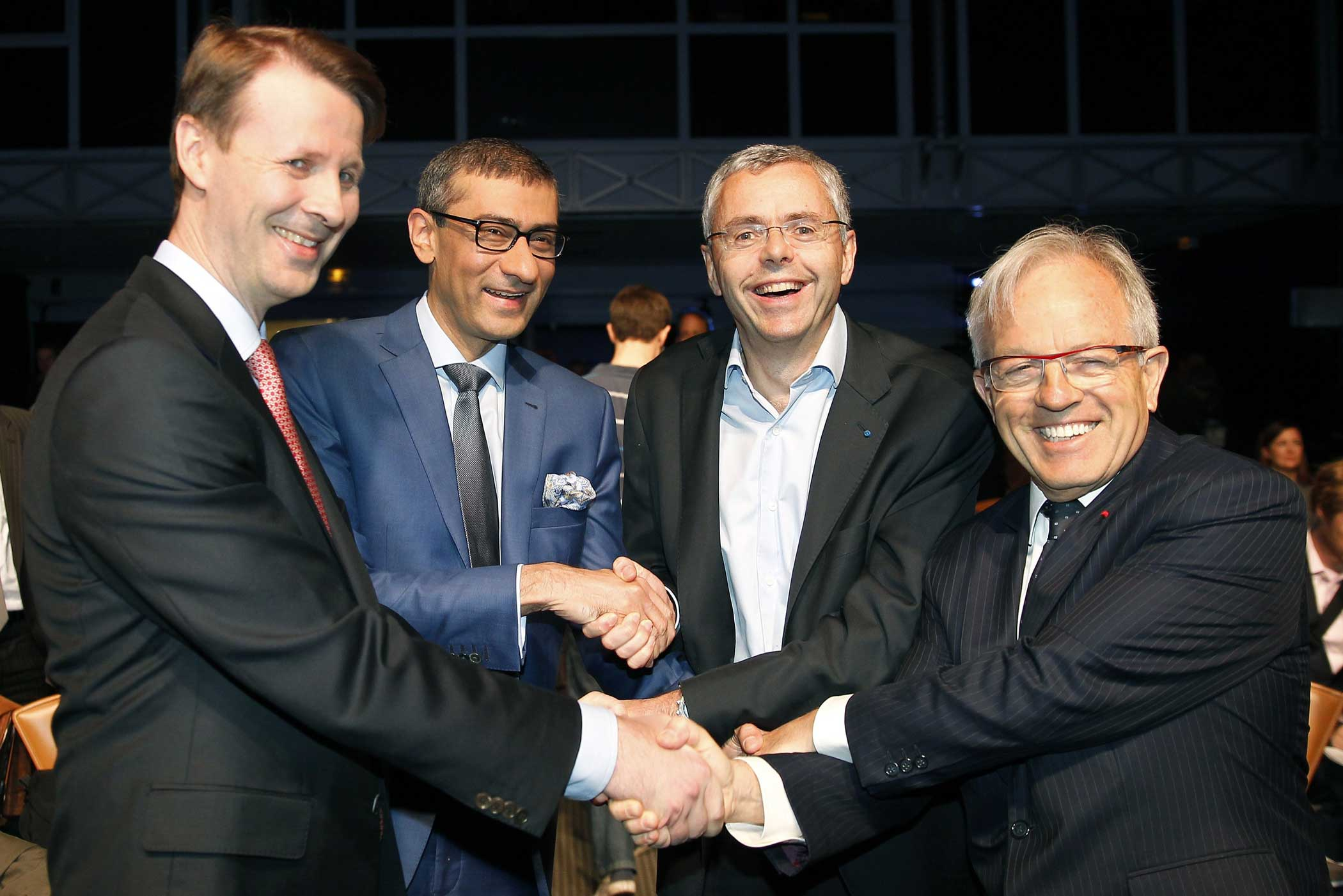 Nokia's chairman Risto Siilasmaa, Nokia's Chief Executive Rajeev Suri, telecommunications company Alcatel-Lucent's Chief Executive Officer Michel Combes and Alcatel-Lucent's chairman of the supervisory board Philippe Camus shake hands prior a press conference on April 15, 2015 in Paris.