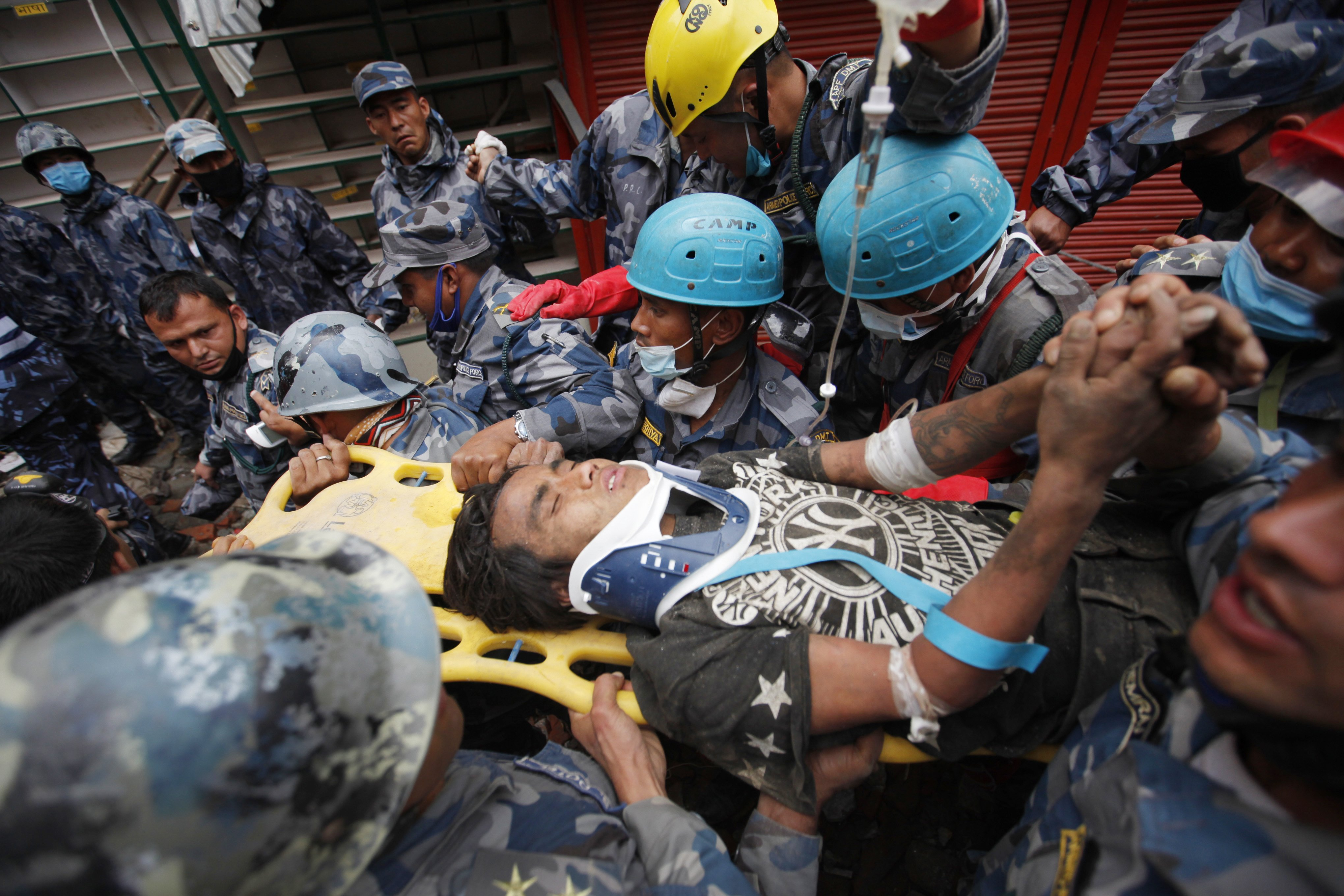 Pemba Tamang is carried on a stretcher after being rescued by Nepalese policemen and U.S. rescue workers from a building that collapsed five days ago in Kathmandu, Nepal on April 30, 2015.