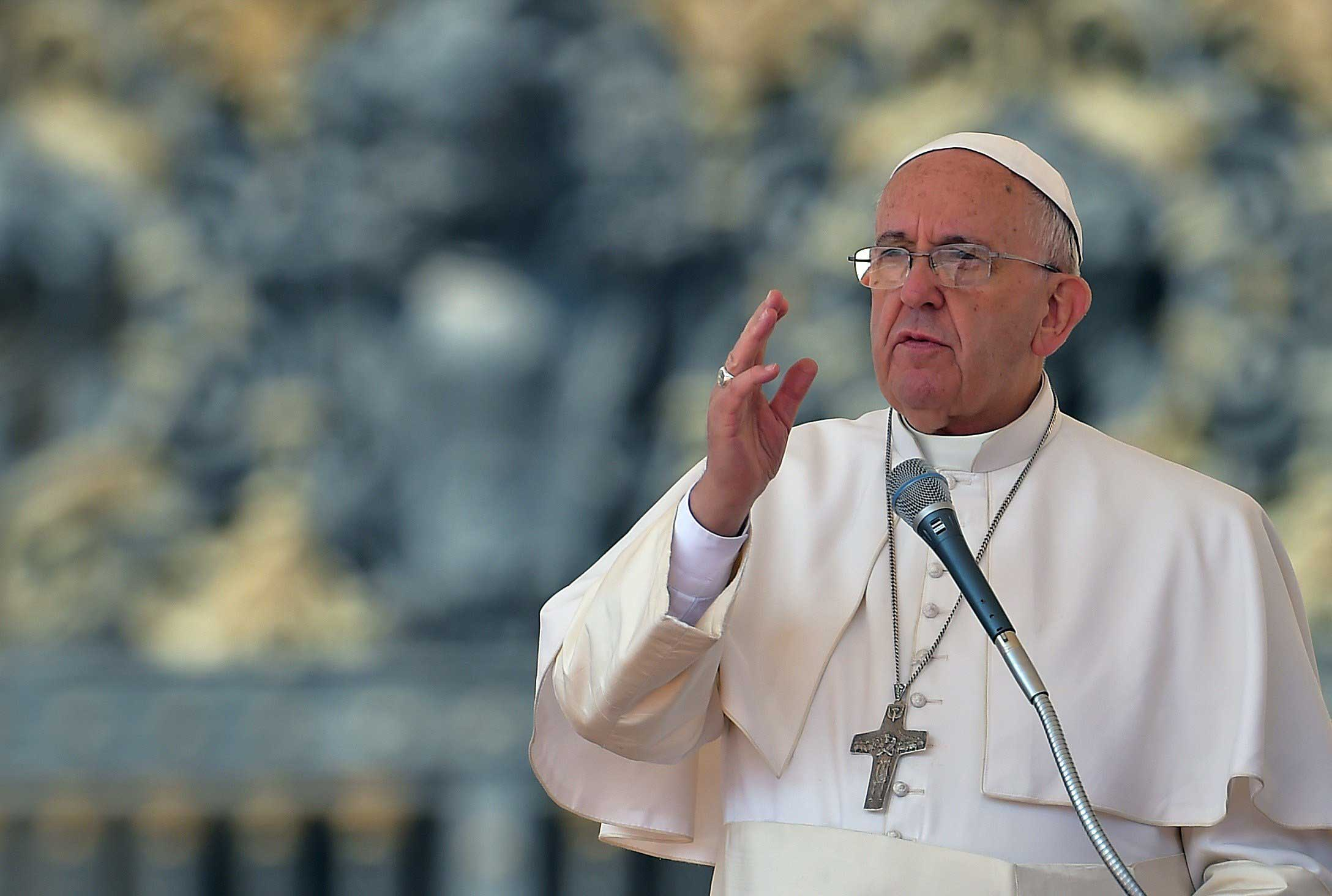 Pope Francis blesses the faithful during his weekly general audience at the Vatican on April 15, 2015.