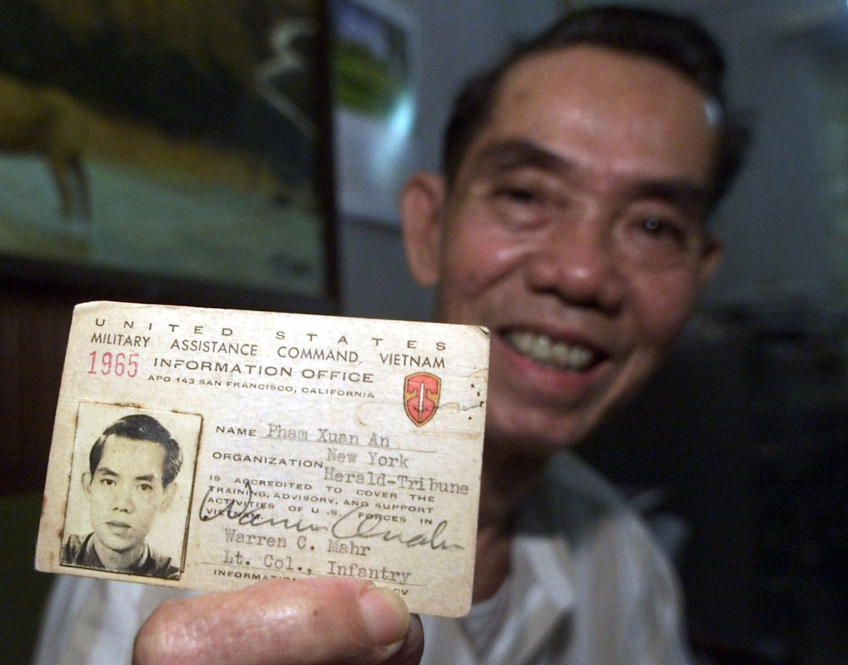 Pham Xuan An holds up his press card from 1965 at his home in Ho Chi Minh City, Vietnam, on April 26, 2000