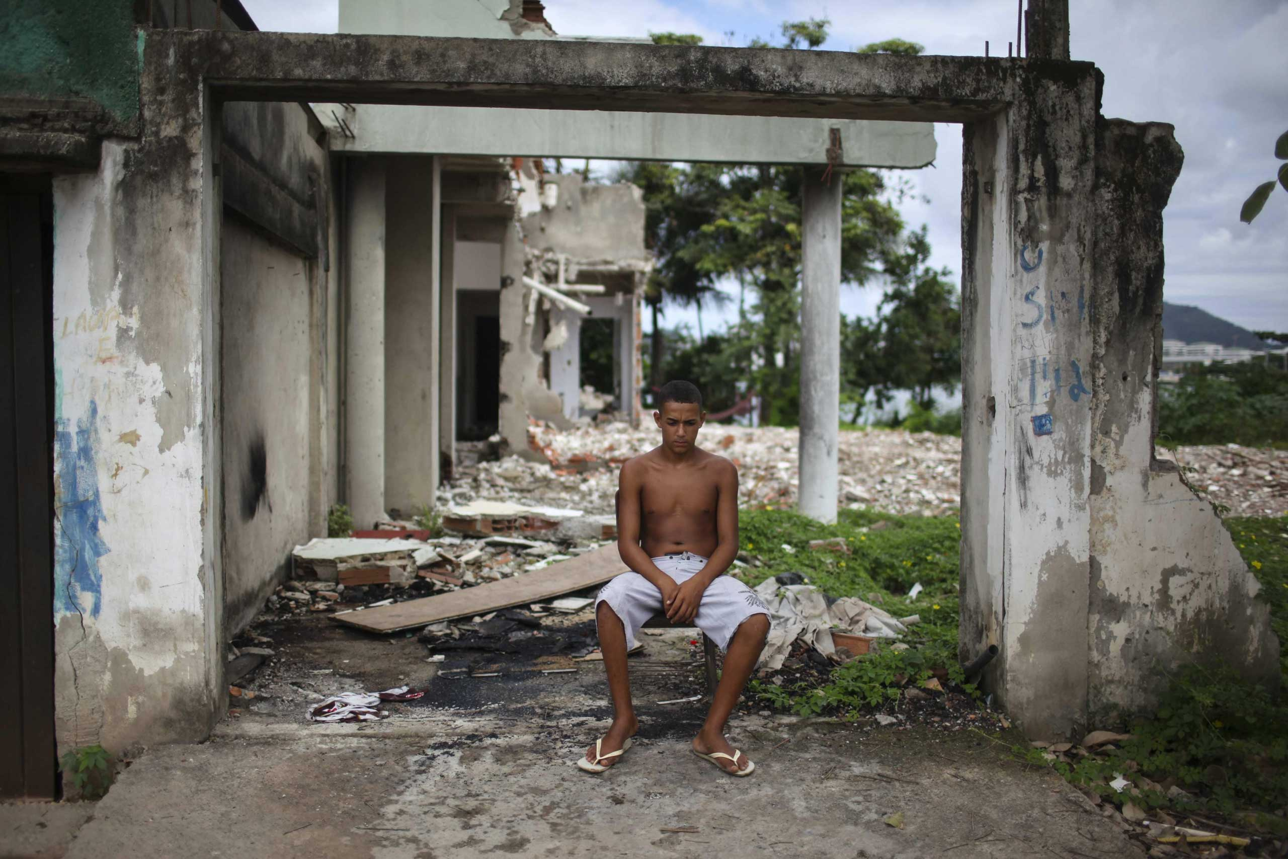 A young man rests next to a destroyed house at the shanty town Vila Autodromo, which is located close to the Olympic Park built for the Olympic Games Rio 2016, in Rio de Janeiro, Brazil, on 01 April 2015.