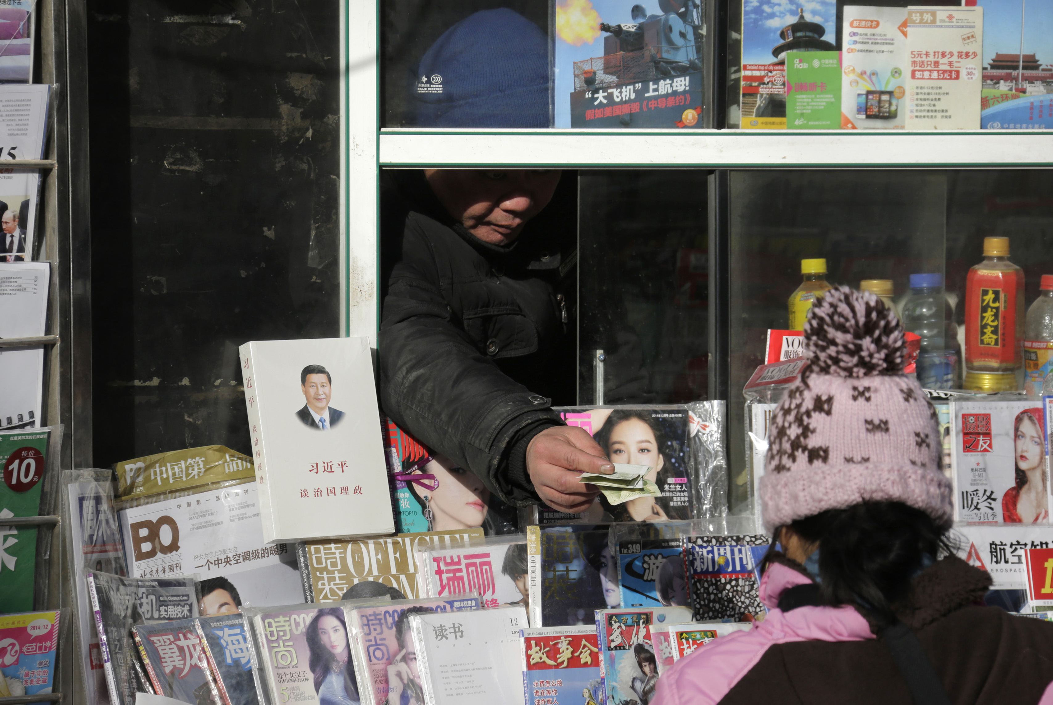 A newsstand vendor returns change to a customer near a book titled Xi Jinping: The Governance of China displayed on sale in central Beijing on Dec. 10, 2014