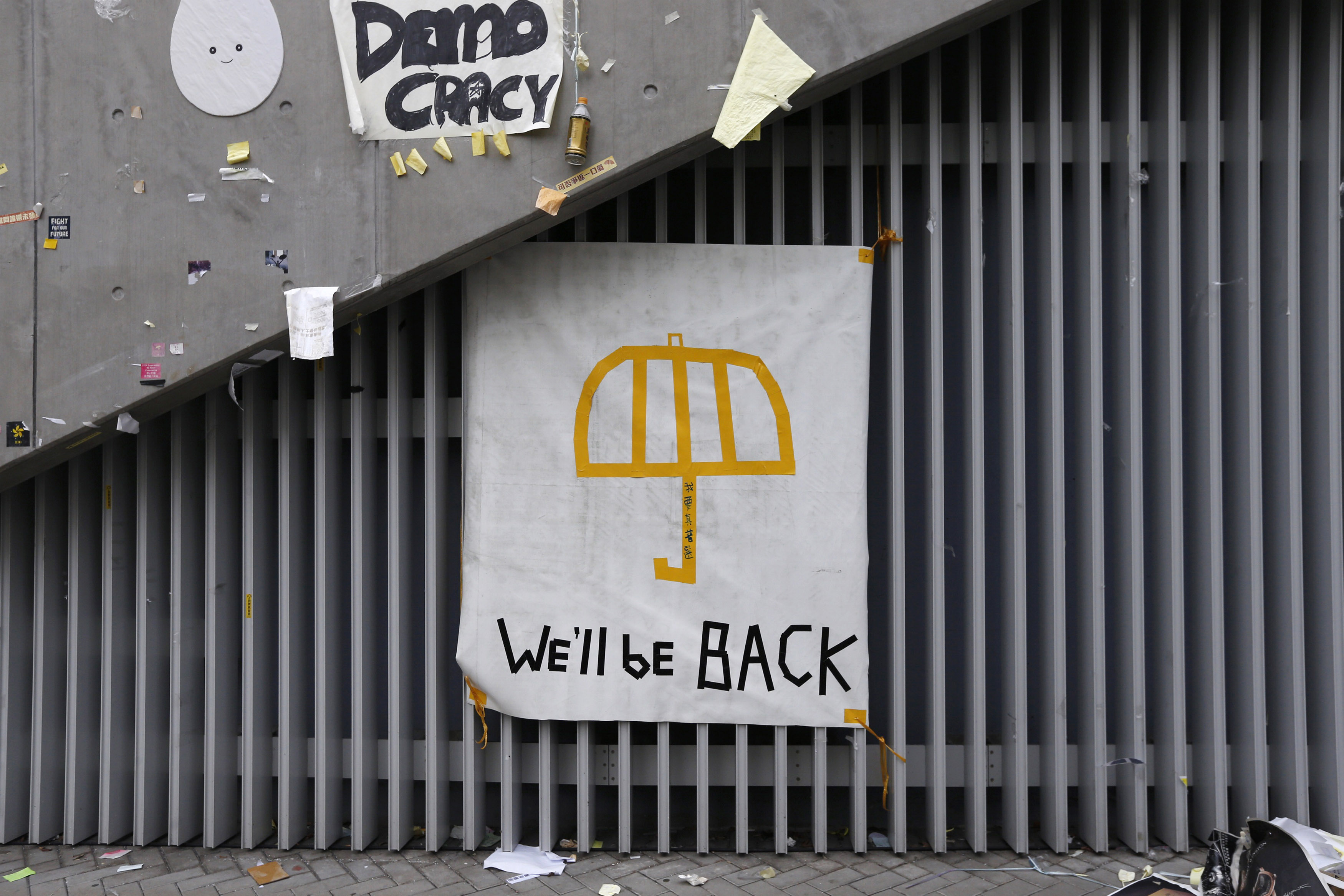 A poster of an umbrella with the words  We'll Be Back  written underneath is pictured on a wall at the main Occupy protest site at Admiralty in Hong Kong on Dec. 11, 2014