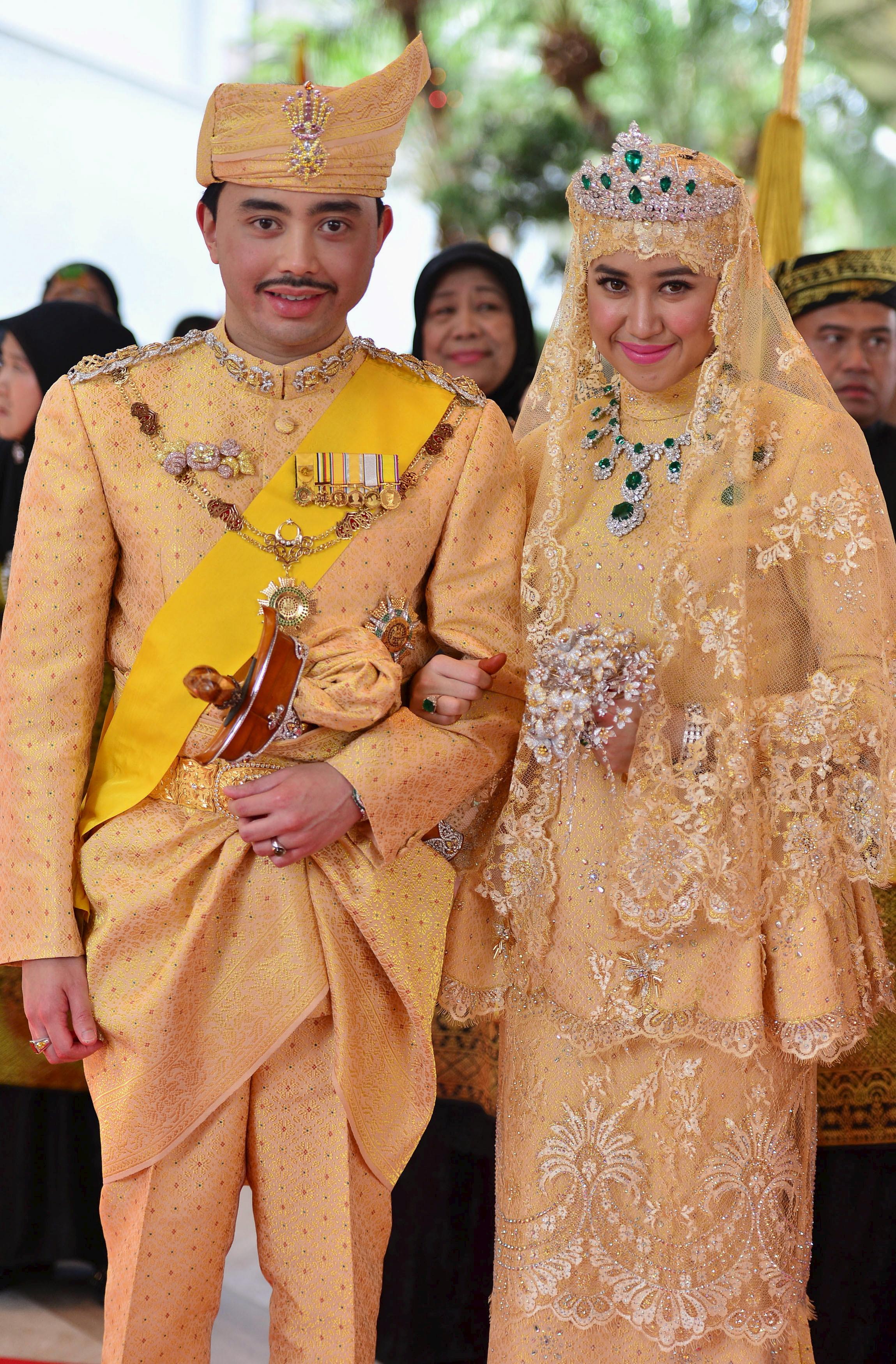Brunei's newly wed royal couple, Prince Abdul Malik and Dayangku Raabi'atul 'Adawiyyah Pengiran Haji Bolkiah, pose for photographers after the  bersanding  or enthronement ceremony at their wedding in the Nurul Iman Palace in Bandar Seri Begawan, Brunei, on April 12, 2015