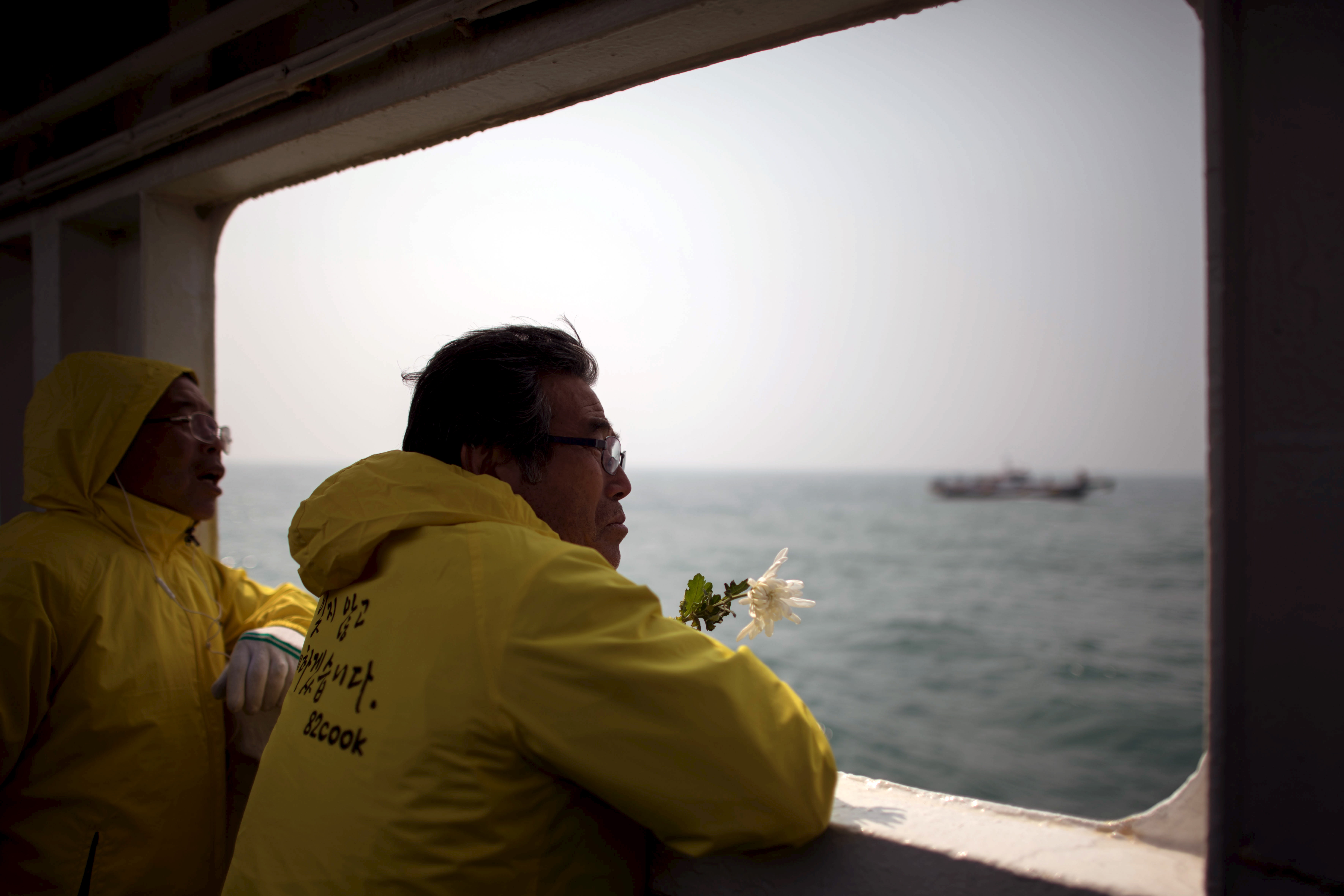 A relative of a victim of the Sewol ferry disaster holds a flower as he stands on the deck of a boat during a visit to the site of the sunken ferry, off the coast of South Korea's southern island of Jindo April 15, 2015