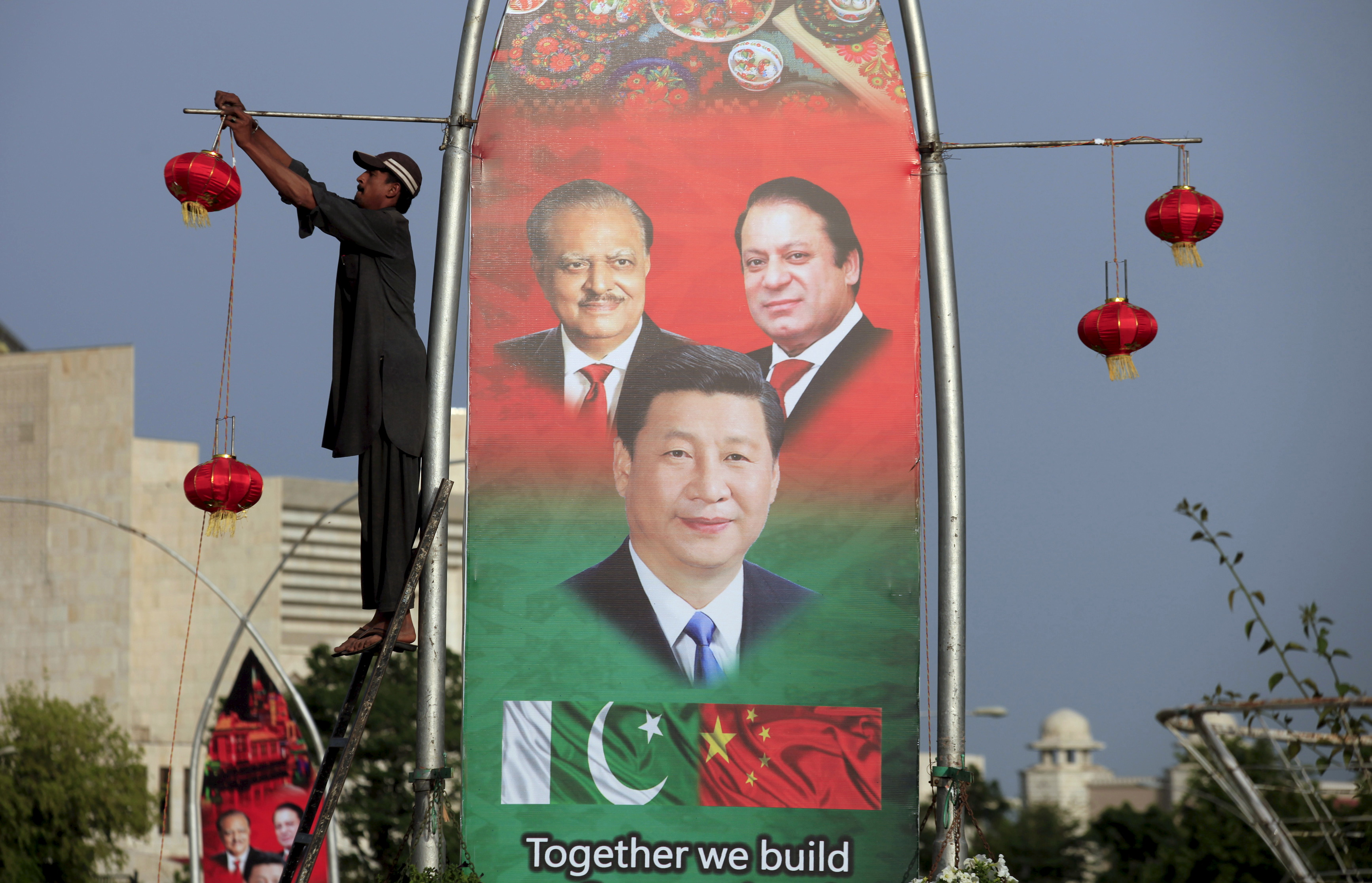 A man hangs decorations on a pole next to a banner showing, clockwise from top left, Pakistani President Mamnoon Hussain, Pakistani Prime Minister Nawaz Sharif and  Chinese President Xi Jinping, on April 19, 2015, ahead of Xi's visit to Islamabad
