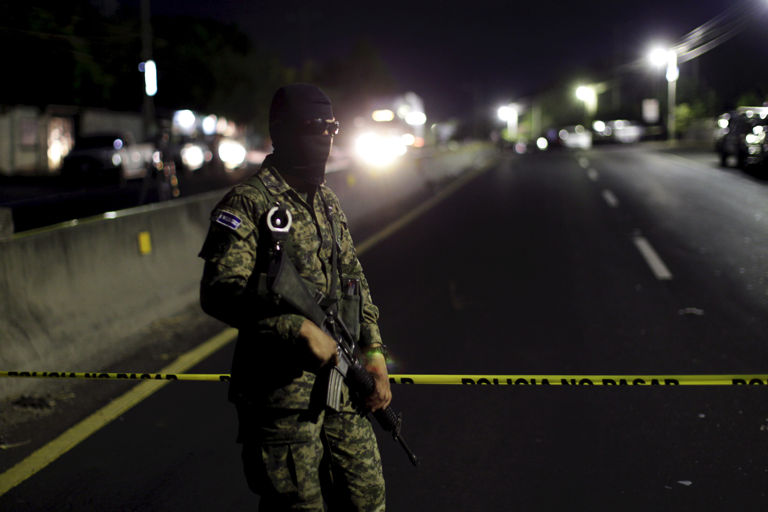 An army soldier guards a crime scene after eight people were shot dead in Quezaltepeque, El Salvador, on March 30, 2015