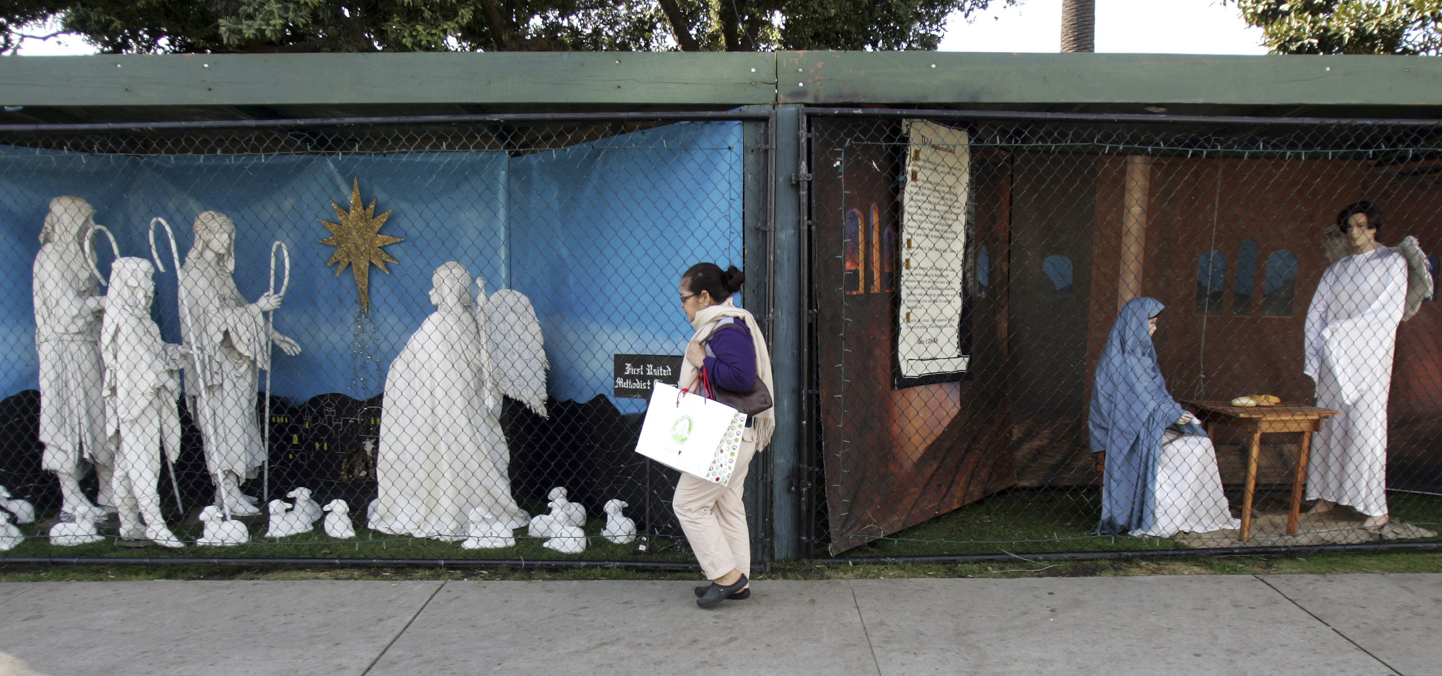 In this Dec. 13, 2011 file photo, a woman walks past a two of the traditional displays showing the Nativity scene along Ocean Avenue at Palisades Park in Santa Monica, Calif.