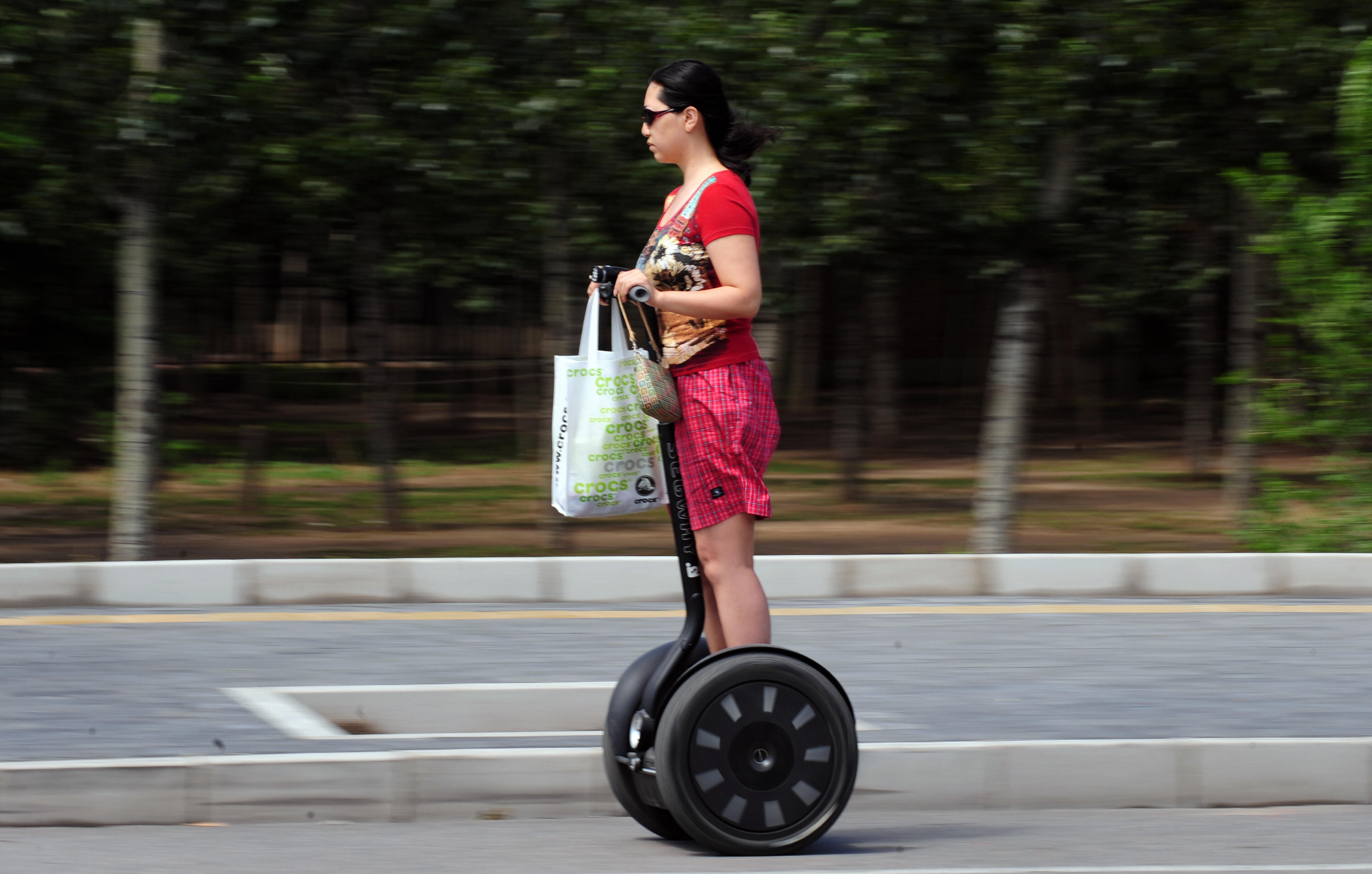 A woman commutes on a Segway electric, self-balancing scooter in Beijing, China, on June 9, 2009.