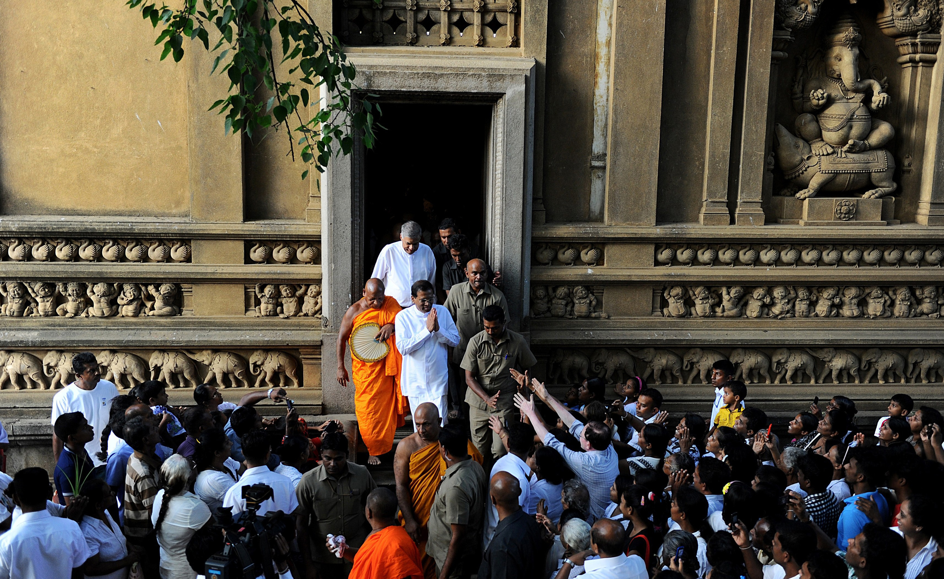 Sirisena, in white with hands together, greets his supporters after praying at a Buddhist temple outside Colombo.