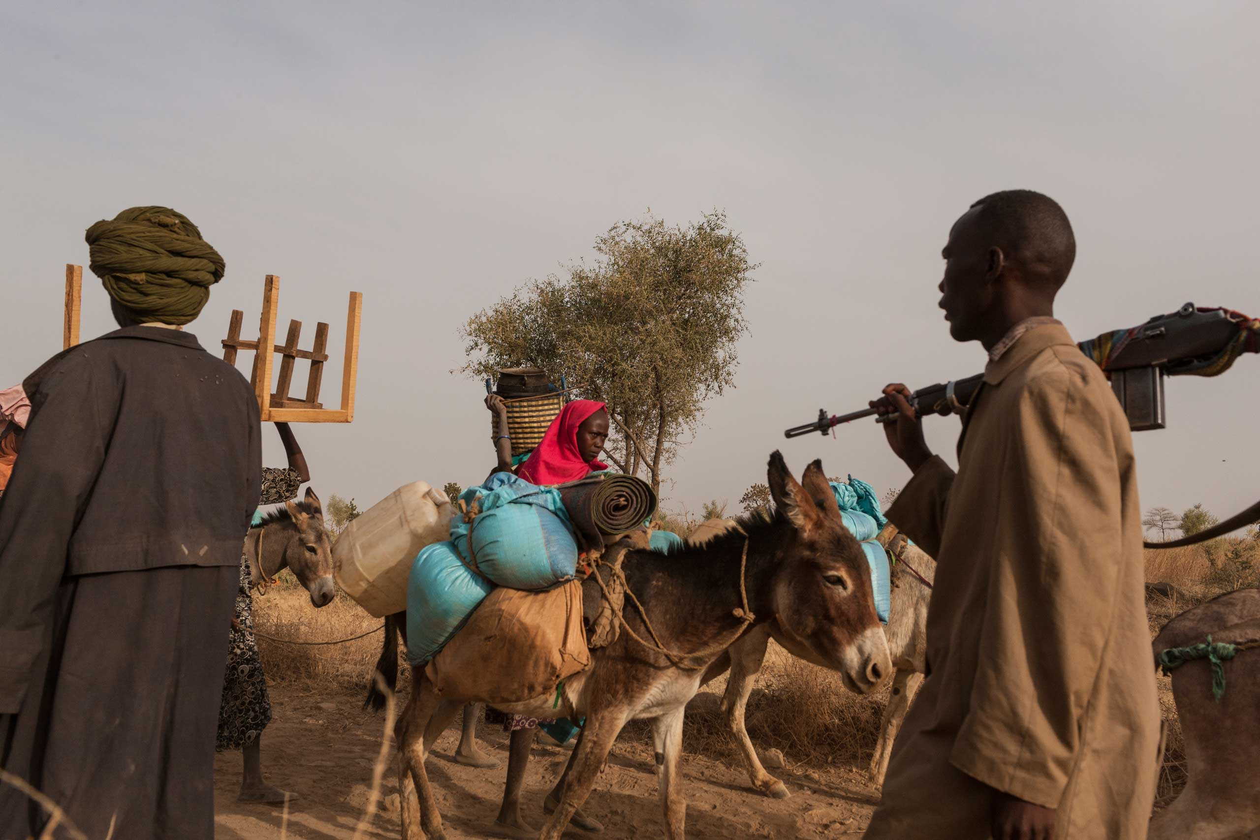 Civilians flee their homes with the few belongings they could carry, while members of the SLA-AW walk toward the front lines in Central Darfur, Sudan, on March 4, 2015.