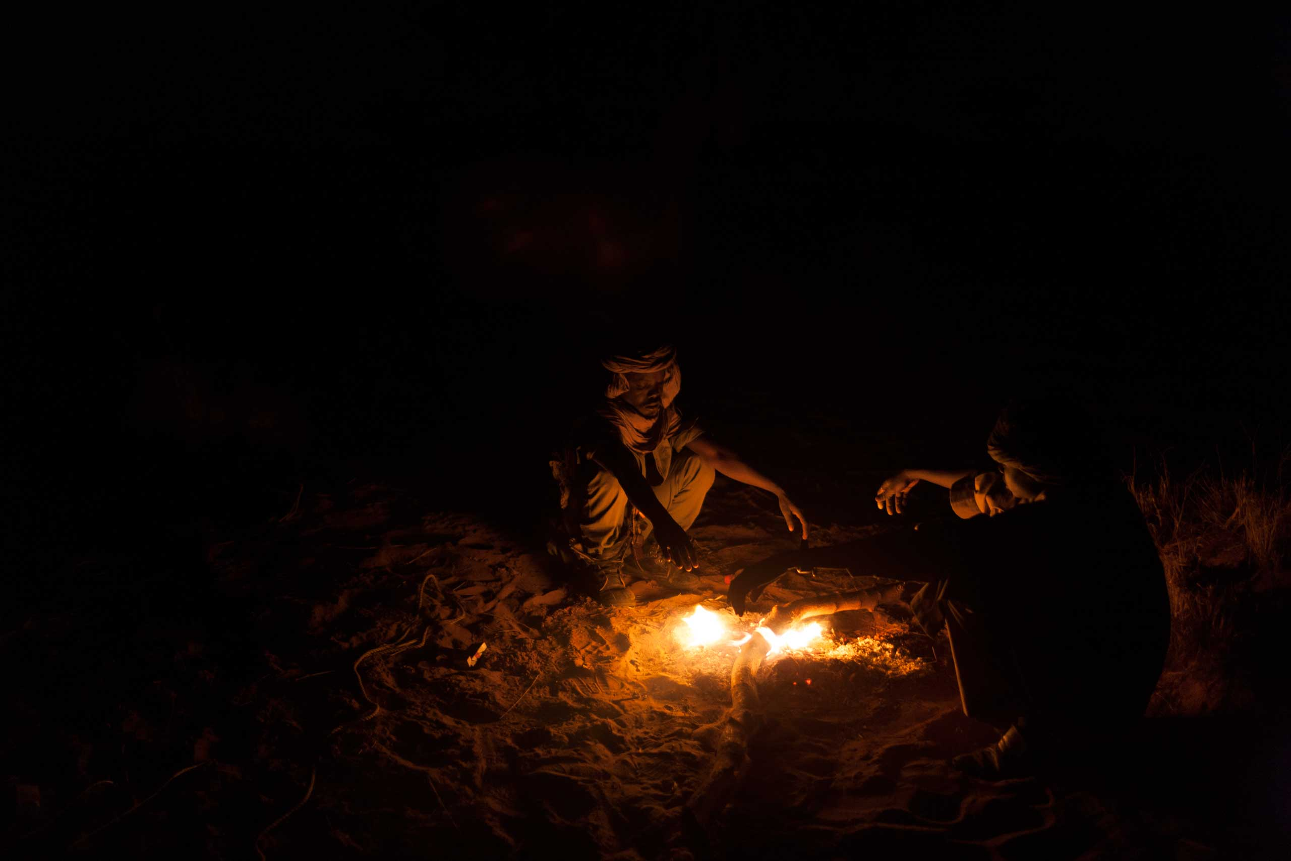 Rebel soldiers from the Sudan Liberation Army – Abdul Wahid (SLA-AW) keep warm by a fire outside their camp in North Darfur, Sudan,  on Feb. 22, 2015.