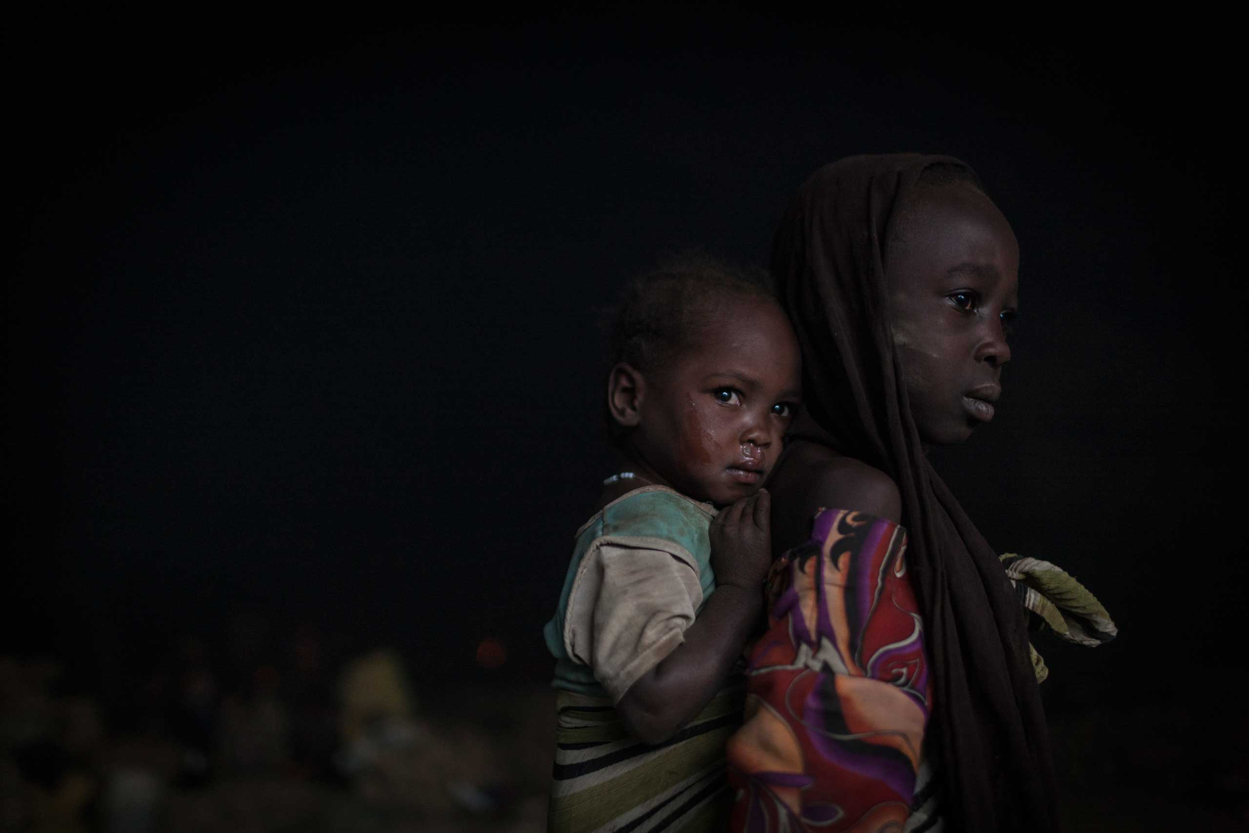 In the early morning, sisters wake up in a cave where they sleep with hundreds of other people whose villages have been destroyed, or who are seeking shelter from bombardment, outside Sarong in Central Darfur, Sudan, March 2, 2015.