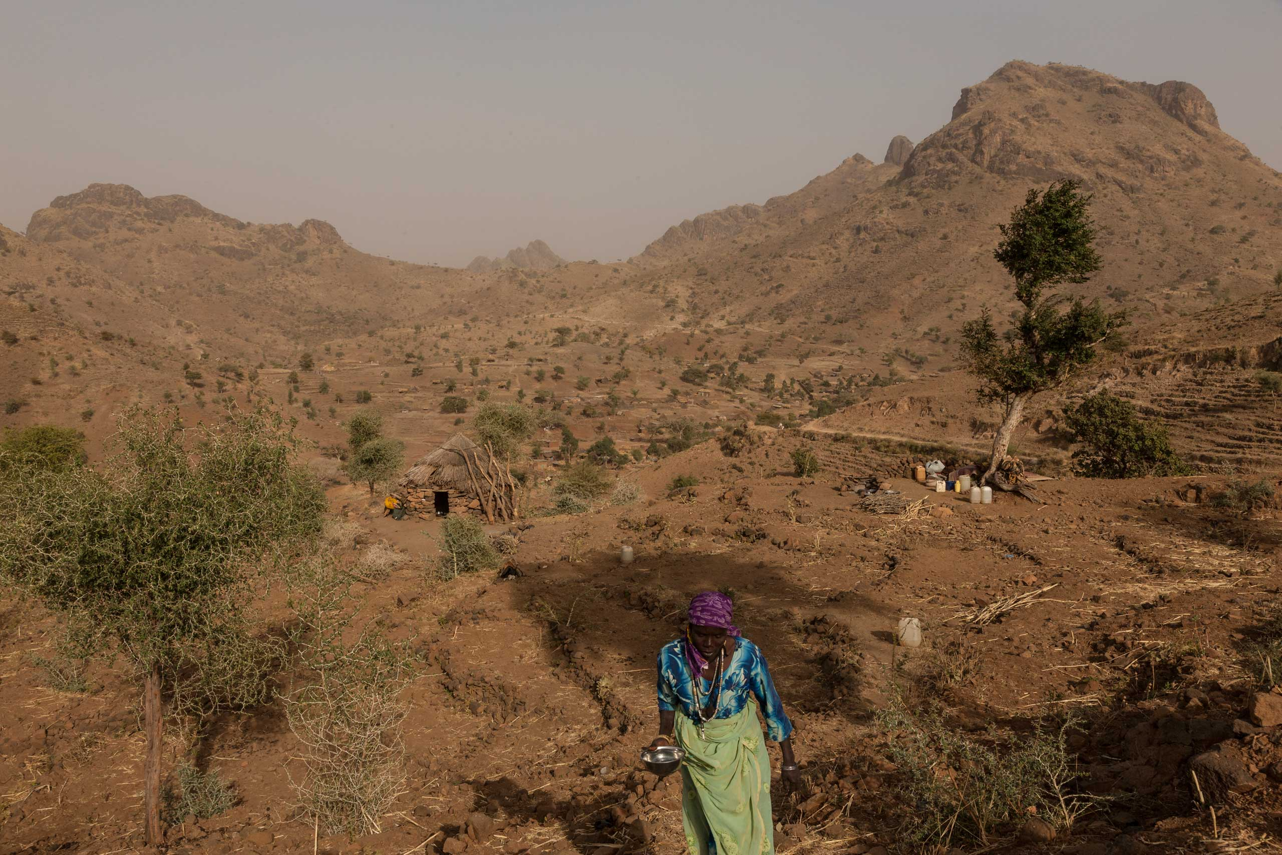 After fleeing a ground attack on the town of Golo on Jan. 24, a woman carries a bowl of water up the mountain from where she lives under a tree outside of Kome in Central Darfur, Sudan, Feb. 28, 2015.