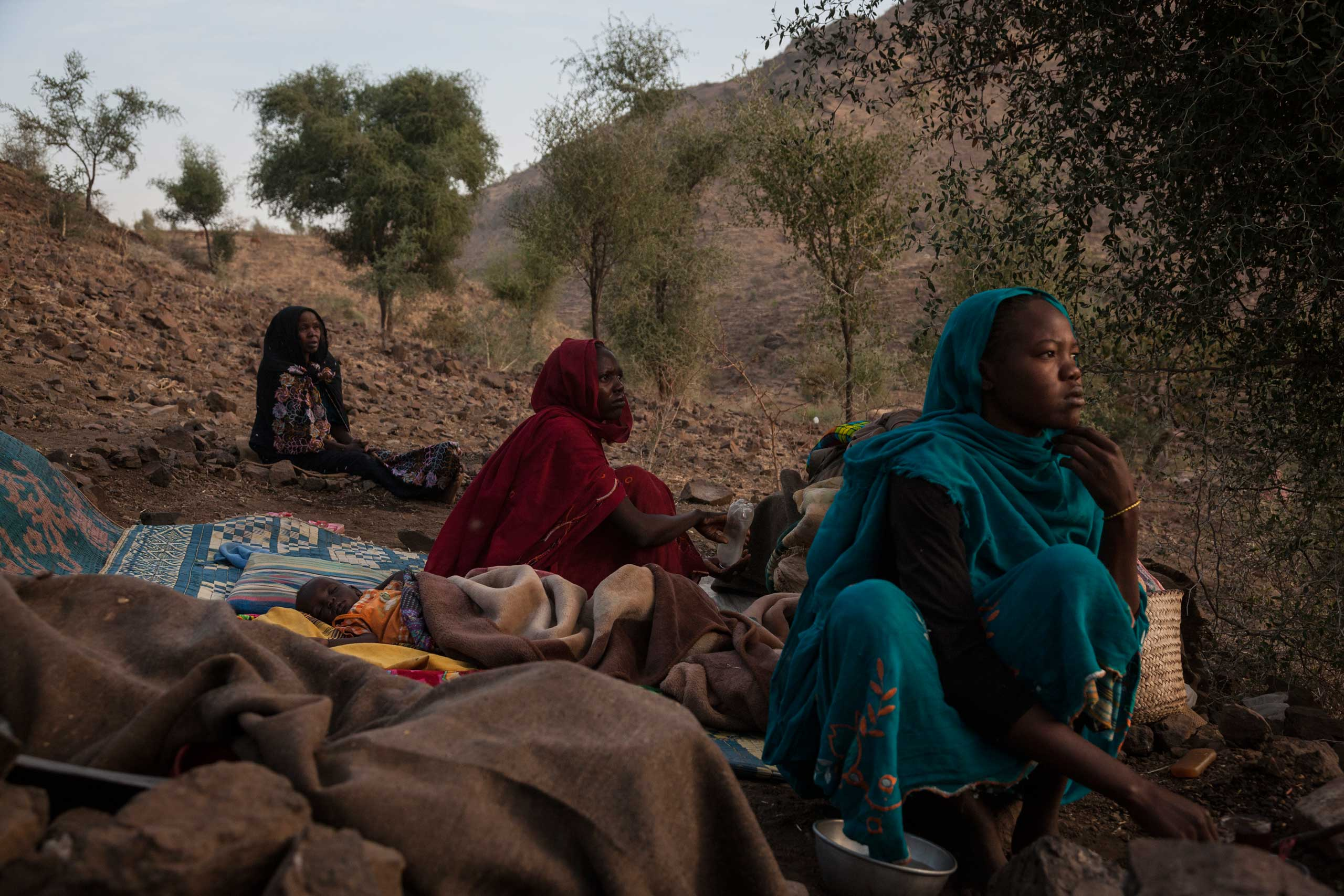 Women from the town of Golo wake up in the morning on the side of a mountain where they sleep outside of Kome in Central Darfur, Sudan, on Feb. 28, 2015.