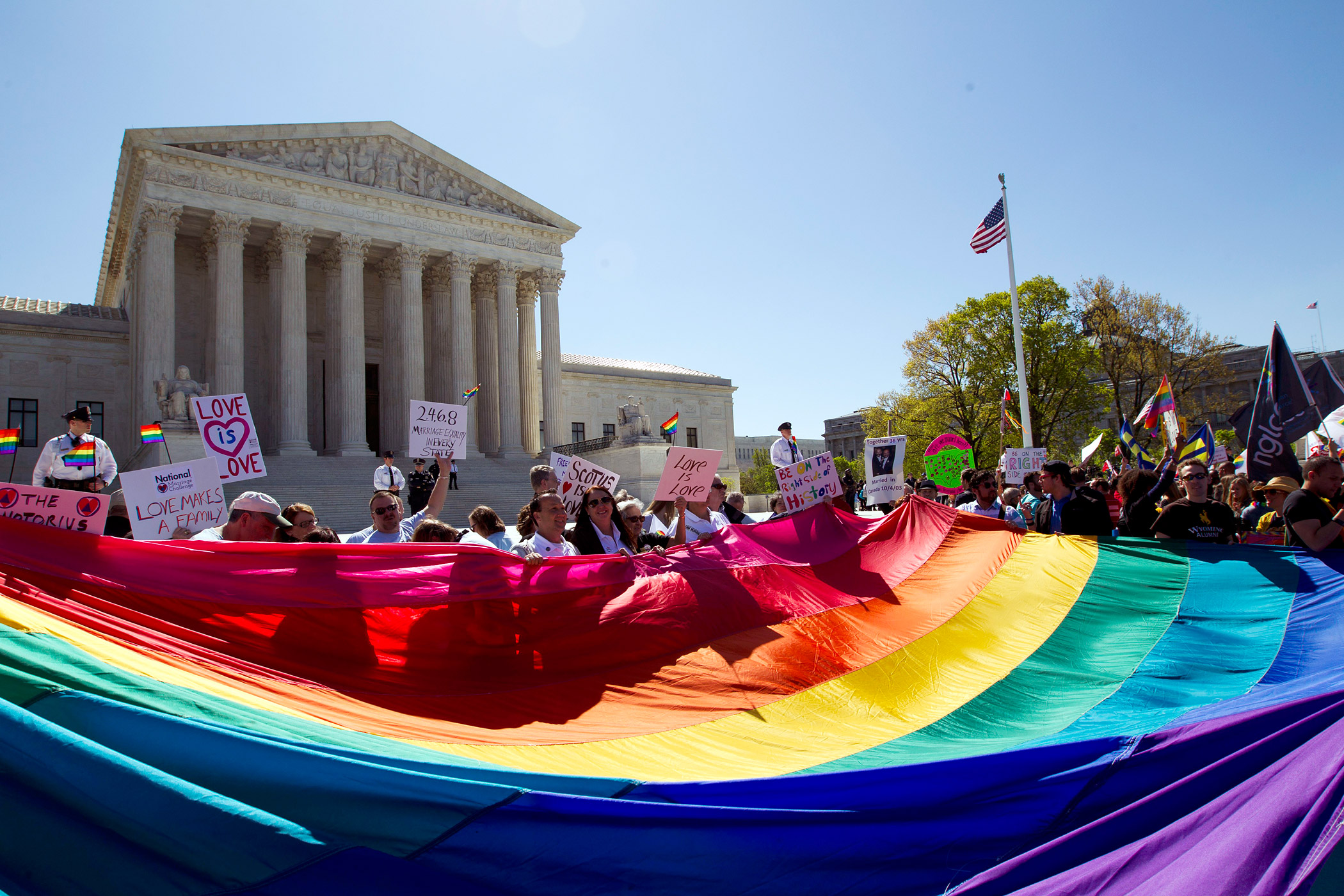 Demonstrators stand in front of a rainbow flag of the Supreme Court in Washington on April 28, 2015.