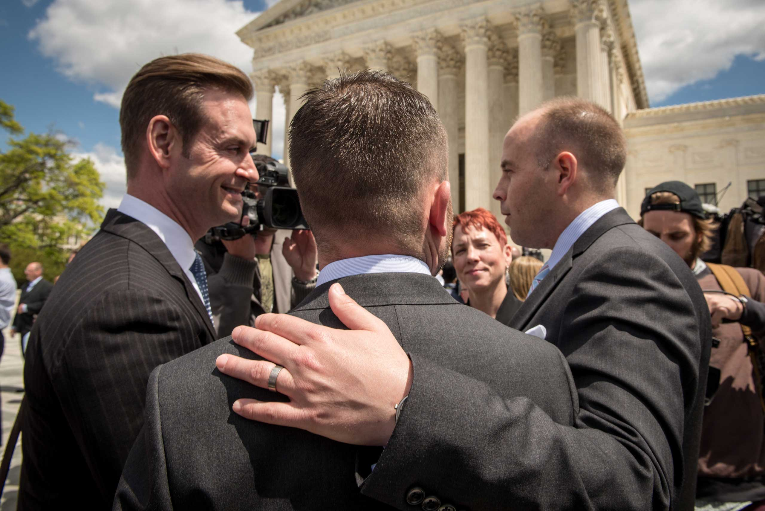 Plaintiffs Thomas Kostra, center and his husband Ijpe Dekoe, right, from Tennessee, speak with the media outside the Supreme Court of the United States following arguments on marriage equality in Washington on April 28, 2015.