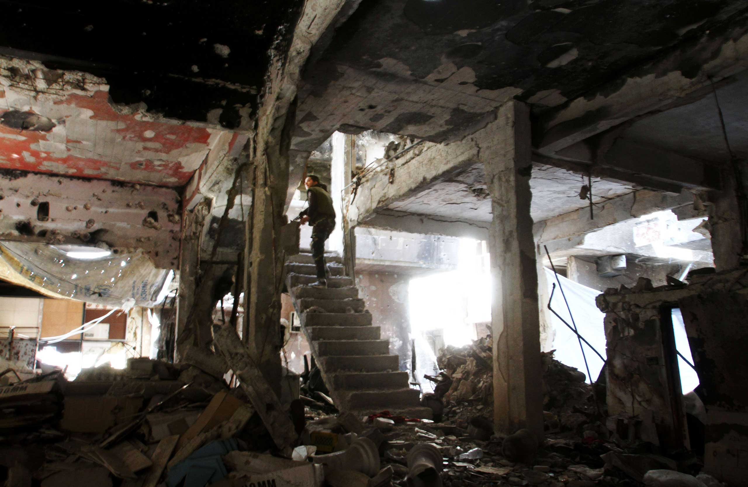 A man stands on a staircase inside a demolished building in the Yarmuk Palestinian refugee camp in the Syrian capital Damascus on April 6, 2015.