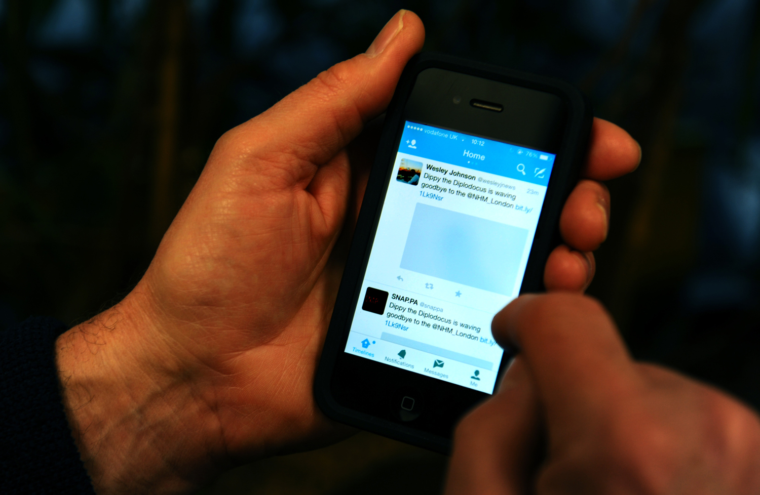 The Twitter App is shown on an Apple iPhone 4S.