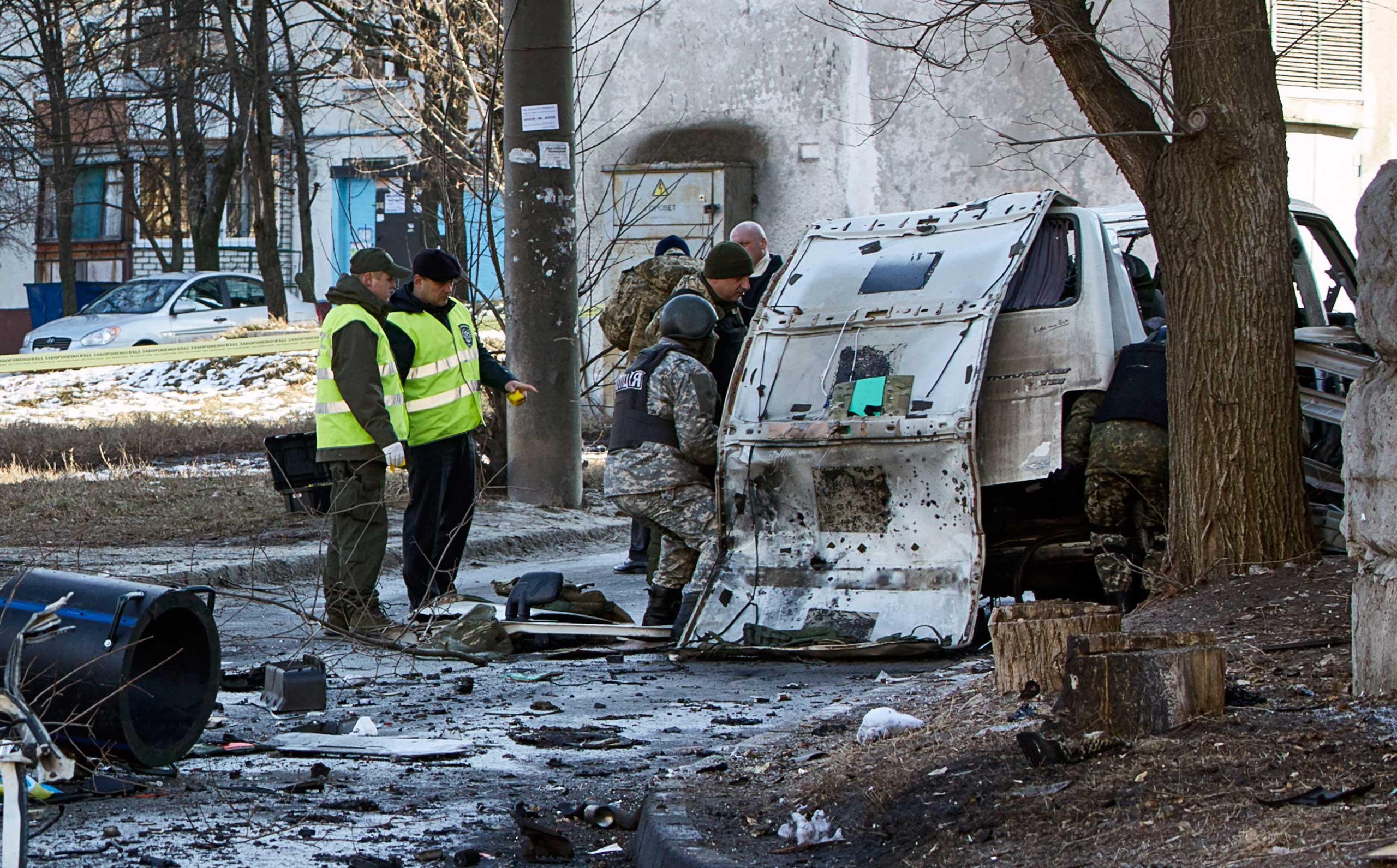 Ukrainian police and forensic experts examine the wreckage of a mini-bus after explosion, in Kharkov, March 6, 2015.