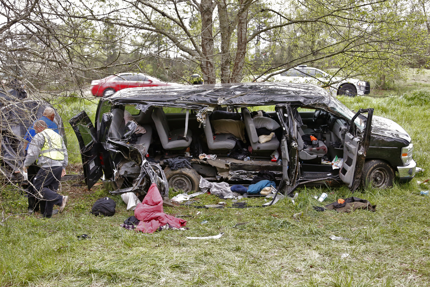 Investigators work at the scene where three people died on April 6, 2015, when a van carrying members of two heavy-metal bands crashed near the town of Commerce, Ga.